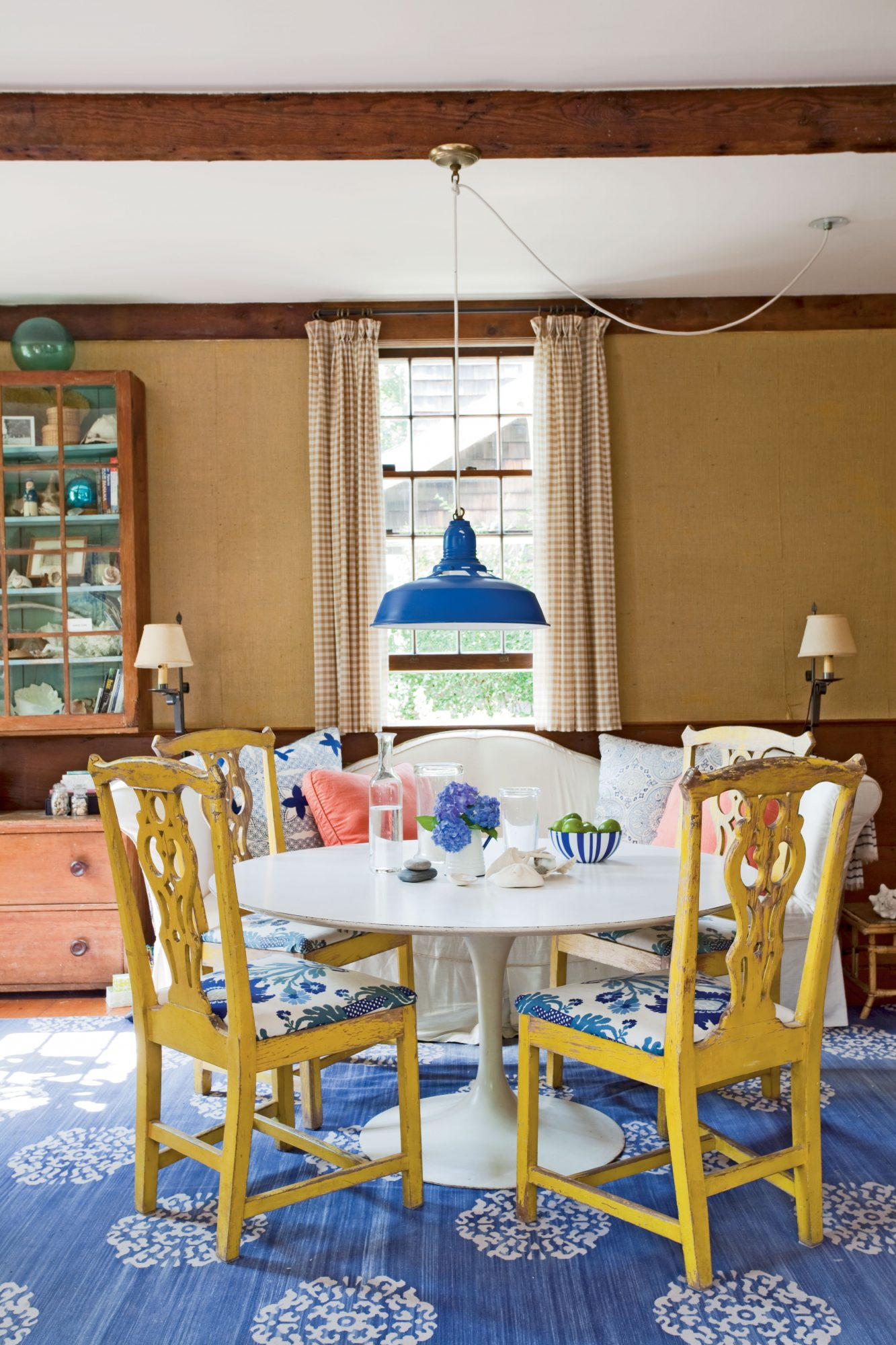 The once-dingy white industrial pendant light was simply utilitarian before being doused with cobalt paint. A coat of sunny yellow takes the Chippendale chairs from traditional to kicky with the stroke of a paintbrush. Mixing finishes like what's on these tables and chairs adds textual variety.