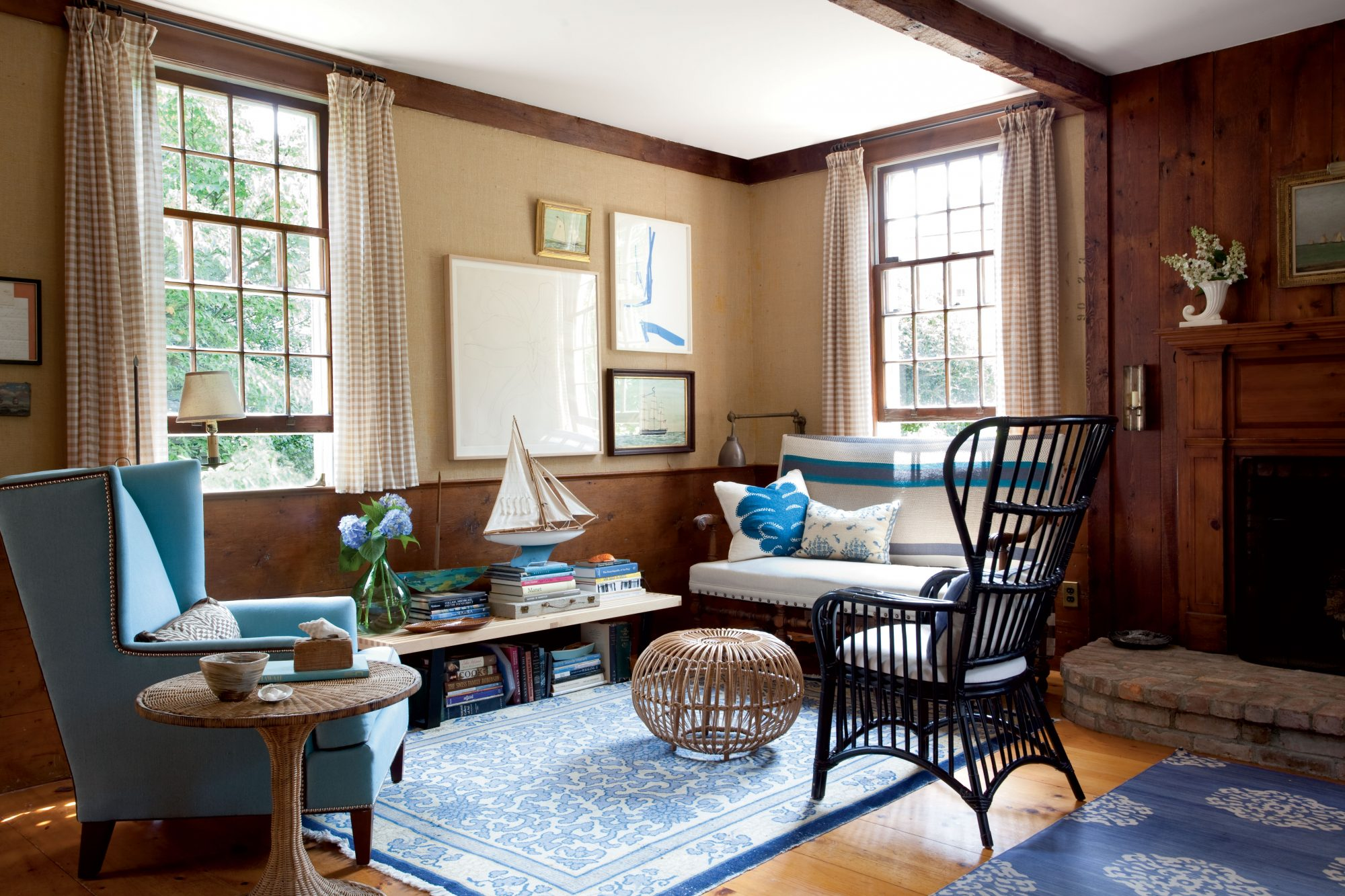 Light wicker furniture and a soft blue wing chair balance the heavier wood of the living room. For a super-casual, camplike feel, try hemming the curtains so they hit just at the windowsills. This look works especially well in rooms with high ceilings and wainscoting, which provides a natural visual cue for the shorter length.