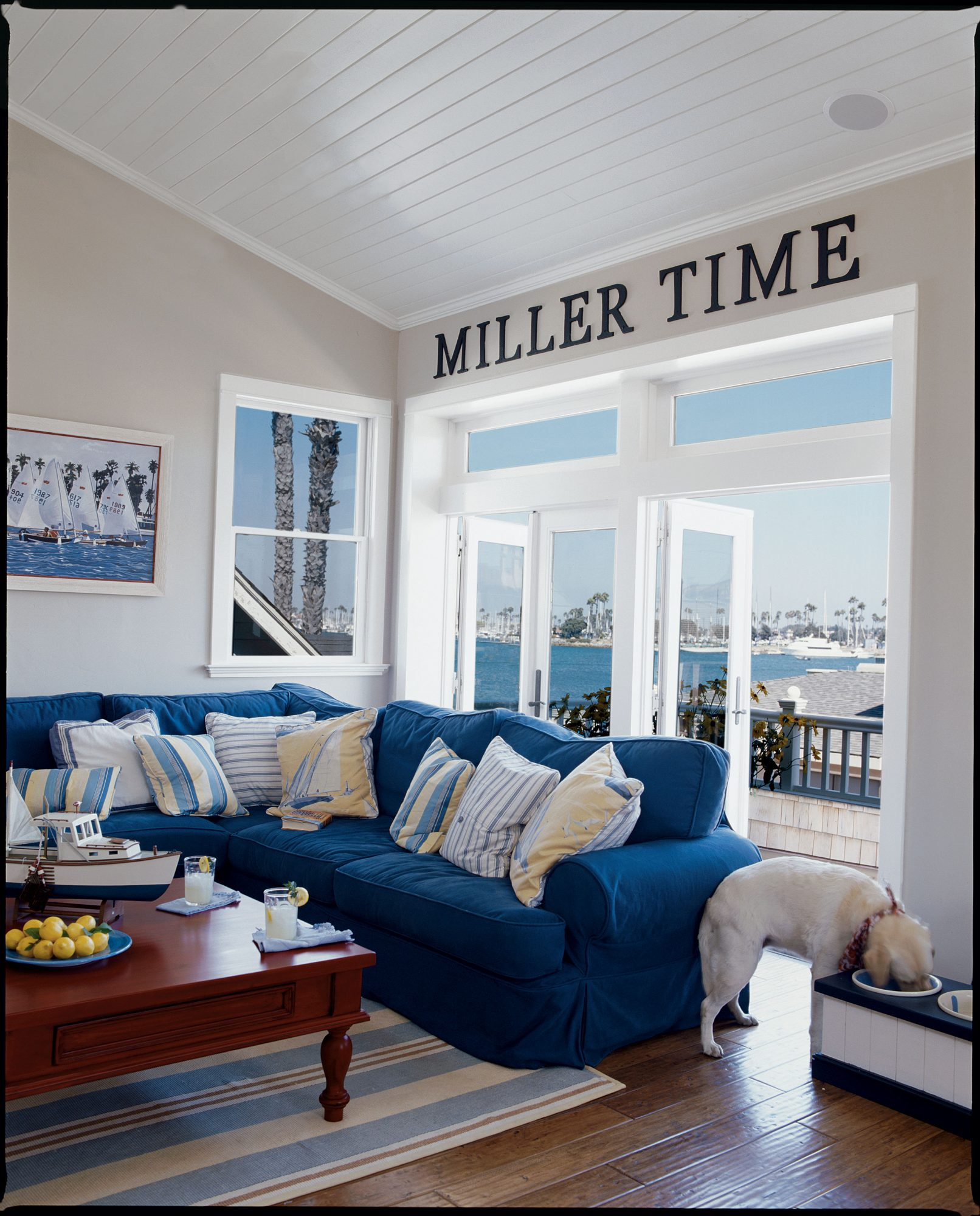 """Big, wooden letters above the family room's French doors spell out the couple's motto. """" 'Miller Time' is being surrounded by family and friends on the beach and enjoying the house,"""" the homeowner explains. The living room features nautical elements and a sea-inspired color palette. Durable cotton-duck slipcovers and a cotton rug in the family room make cleanup easy in case the party—or the dogs—get out of hand."""