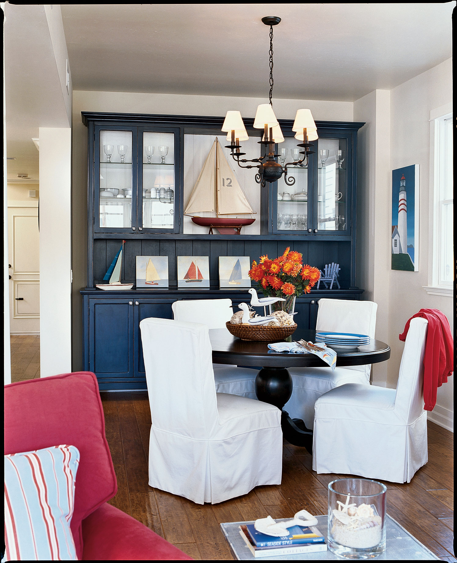 The family's dining room also features nautical elements and a patriotic color palette of red, white, and blue. The homeowners designed the hutch and table, along with other furnishings, to fit the space and their needs.