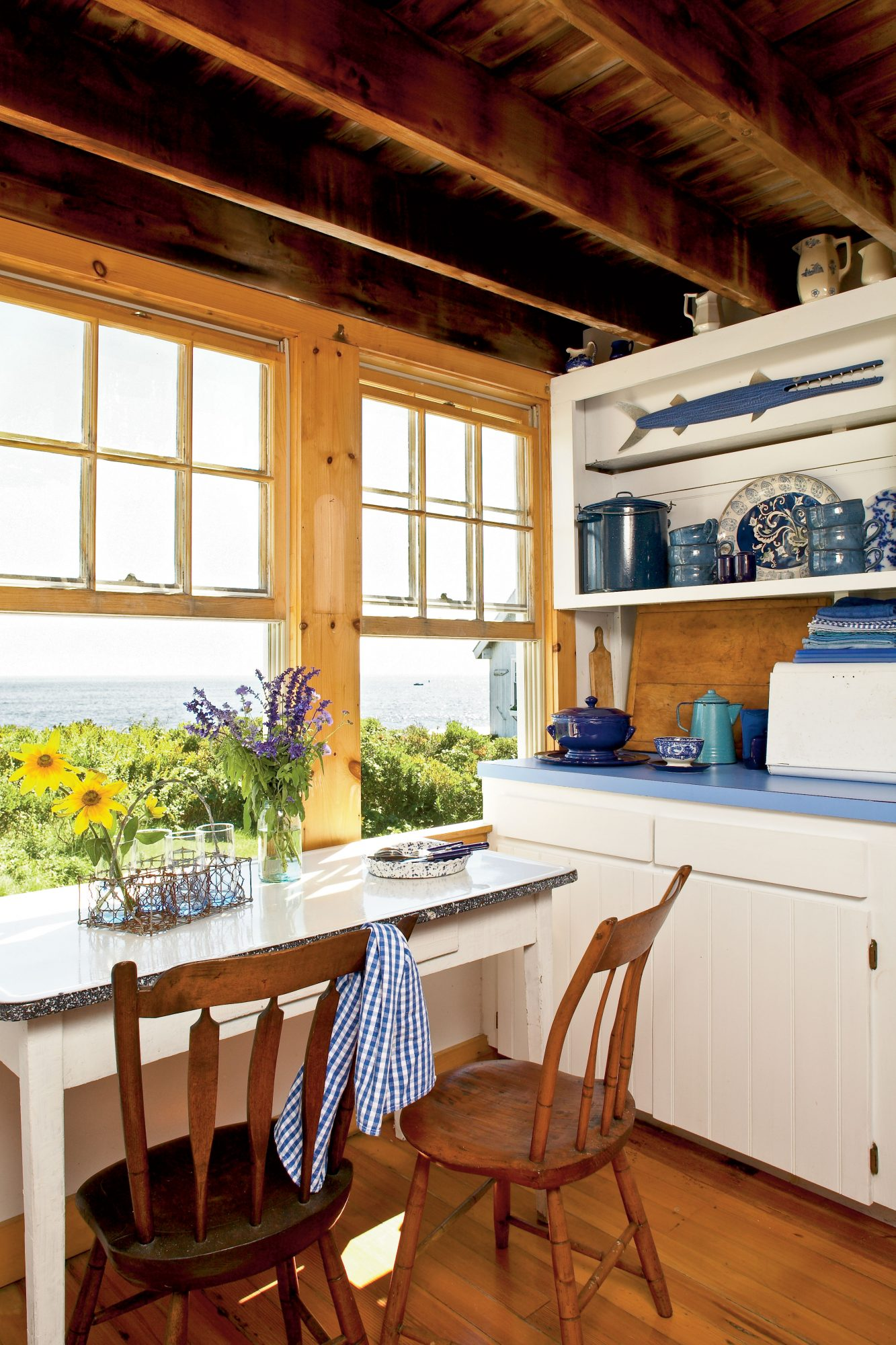 The small breakfast table placed square in front of the windows provides the best view of the waves crashing off Casco Bay. A collection of enamelware in the kitchen's open cabinets came with the house and was—surprisingly—in the homeowner's favorite shades of blue.