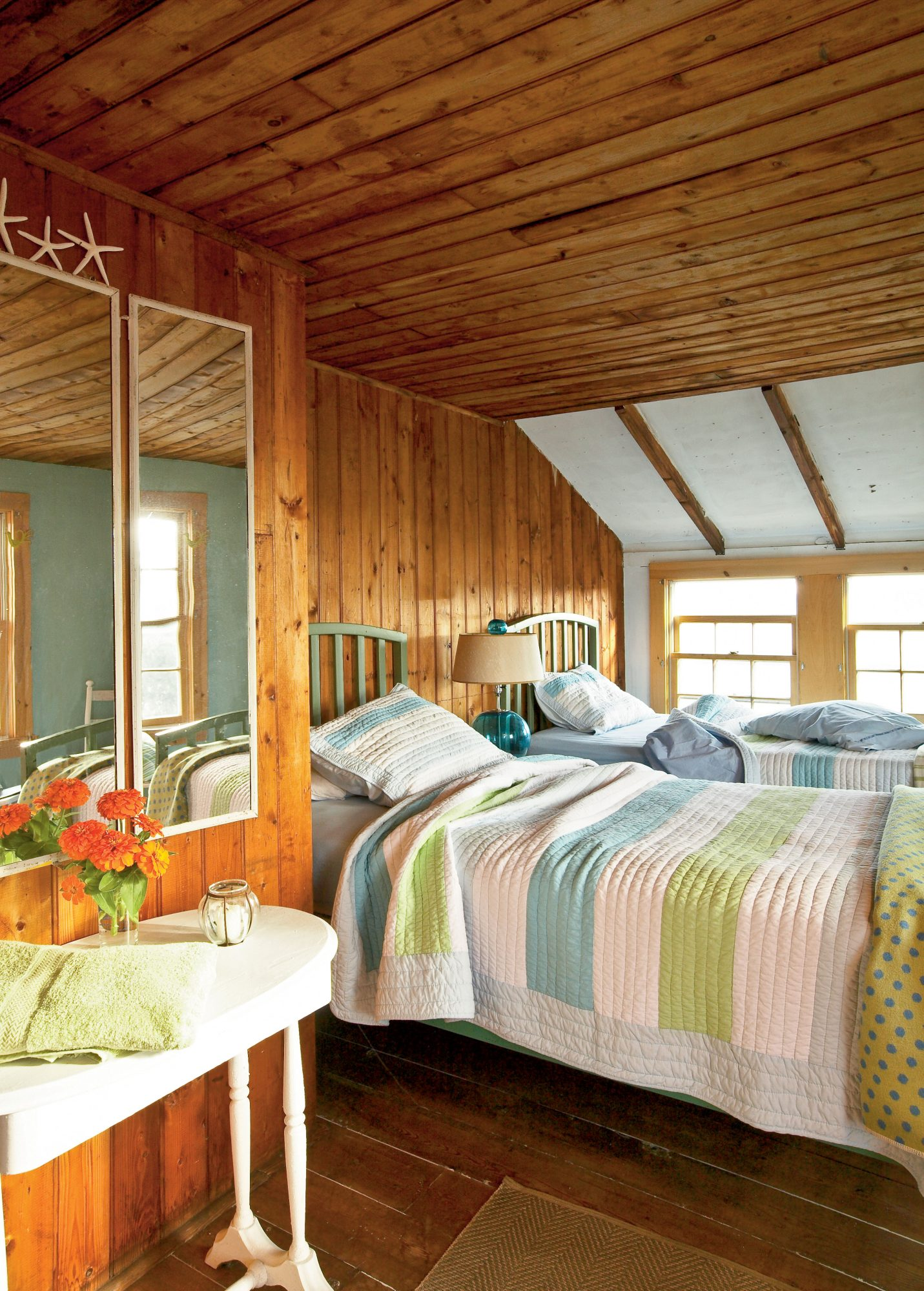 Wood-planked floors and cozy quilts made of light, sea-colored pastels honor the rustic feel of the century-old cottage, embracing the charm of the setting and the house.