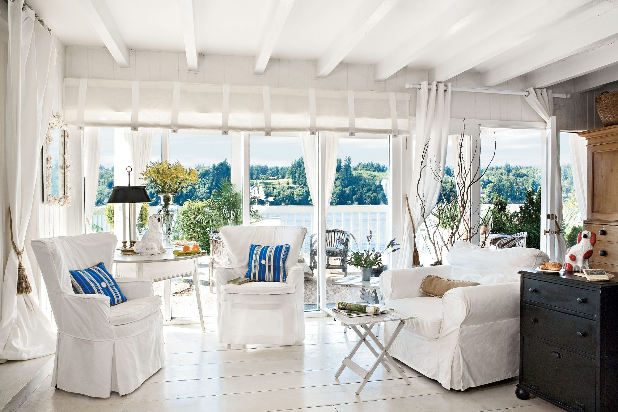To keep things simple in her living room—as to not distract from the gorgeous view—the homeowner used easy-to-wash white slipcovers and hung white linen or cotton draperies and shades on doorways and windows. A little splash of blue from the throw pillows is the only color used.