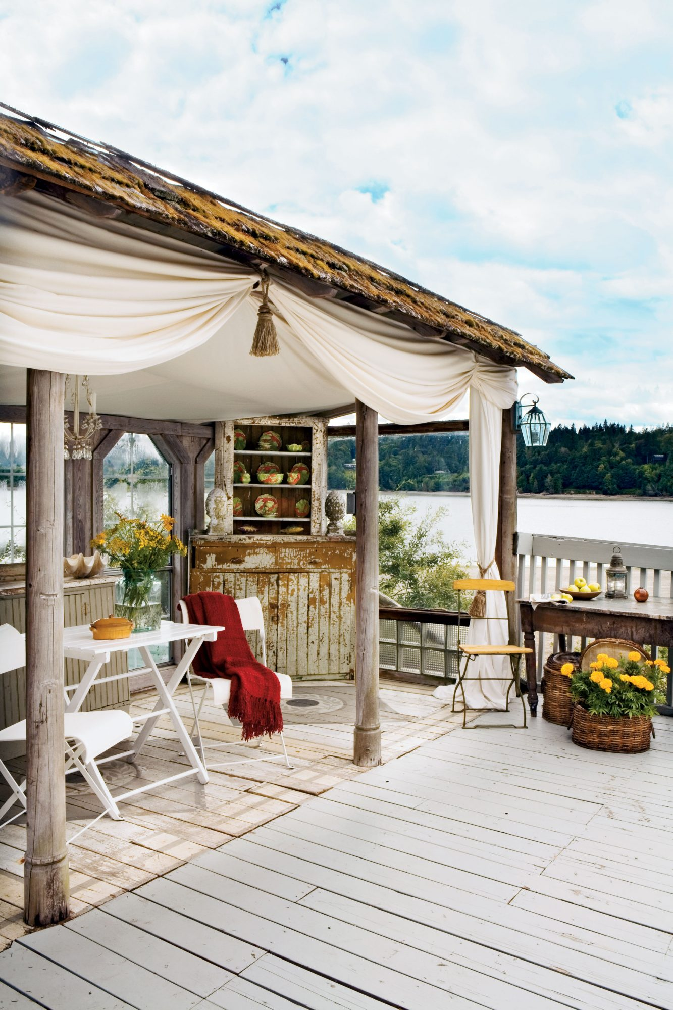 Previous owners built an outdoor room at the end of the main-level deck as a windbreak. The space is outfitted with a hutch, buffet, chandelier, and draperies to make it a comfortable extension of living space.