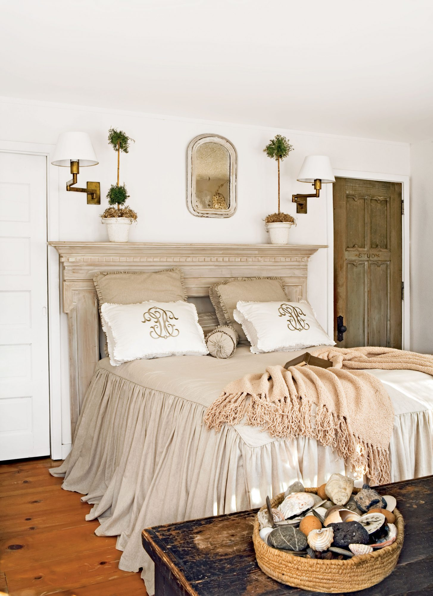 A damaged mantel serves as a headboard in the master bedroom. Because the small space doesn't allow for bedside tables, the homeowner installed sconces for nighttime reading.