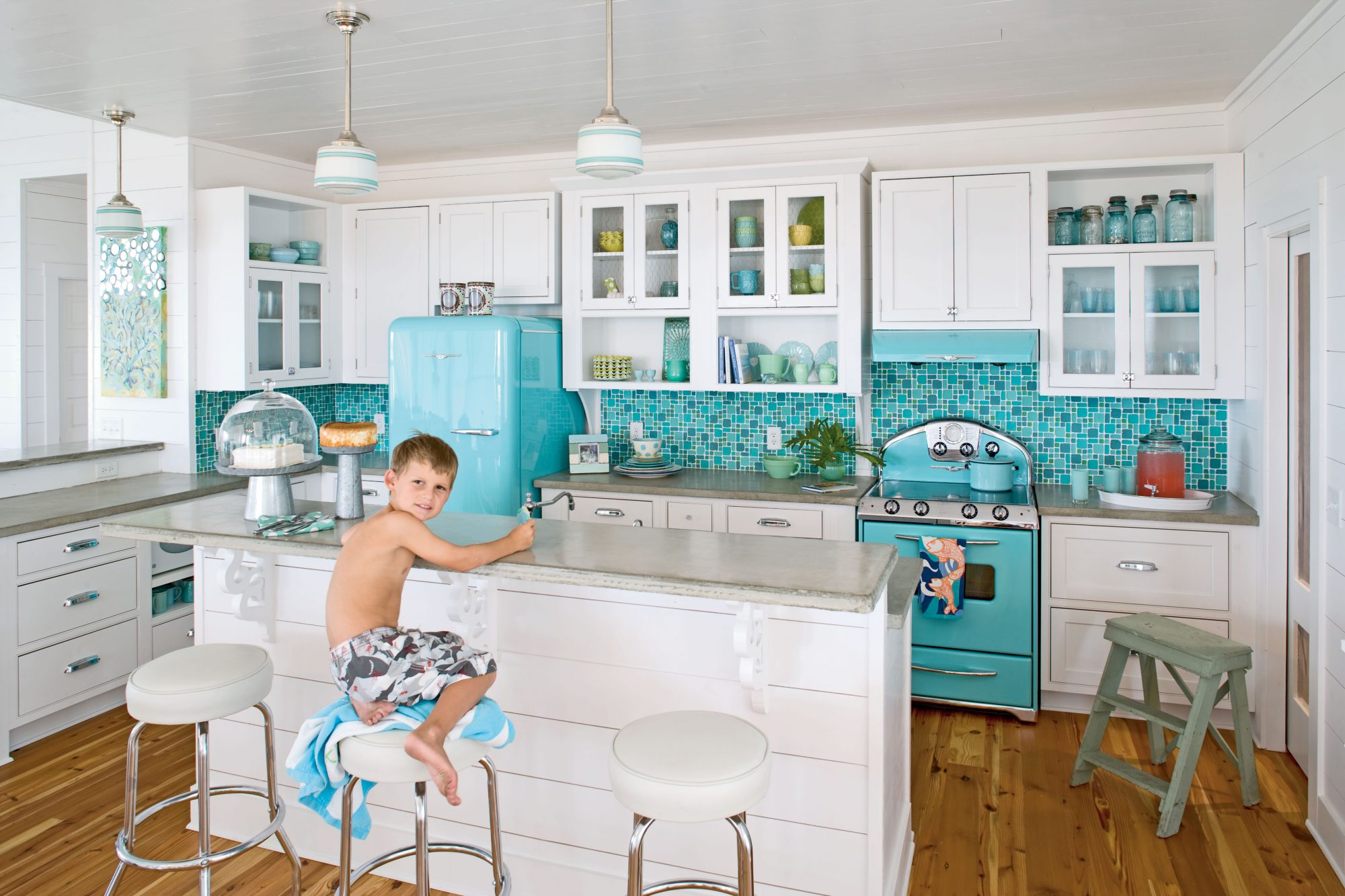 The punchy turquoise hue of the vintage-style appliance puts a chic spin on the space. A tumbled-glass backsplash mimics natural sea glass and contrasts the sleek concrete countertops. Reproduction pendant lighting and period barstools top off the soda fountain look the homeowners hoped to achieve.