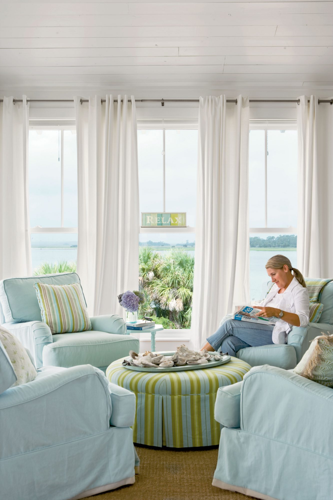 This serene living room came together in a wash of pastels. To promote conversation, designer Jane Coslick opted for four chairs instead of the traditional sofa-centered seating arrangement; she repeated fabric from the dining room on the round ottoman to unify the look of the adjacent rooms.