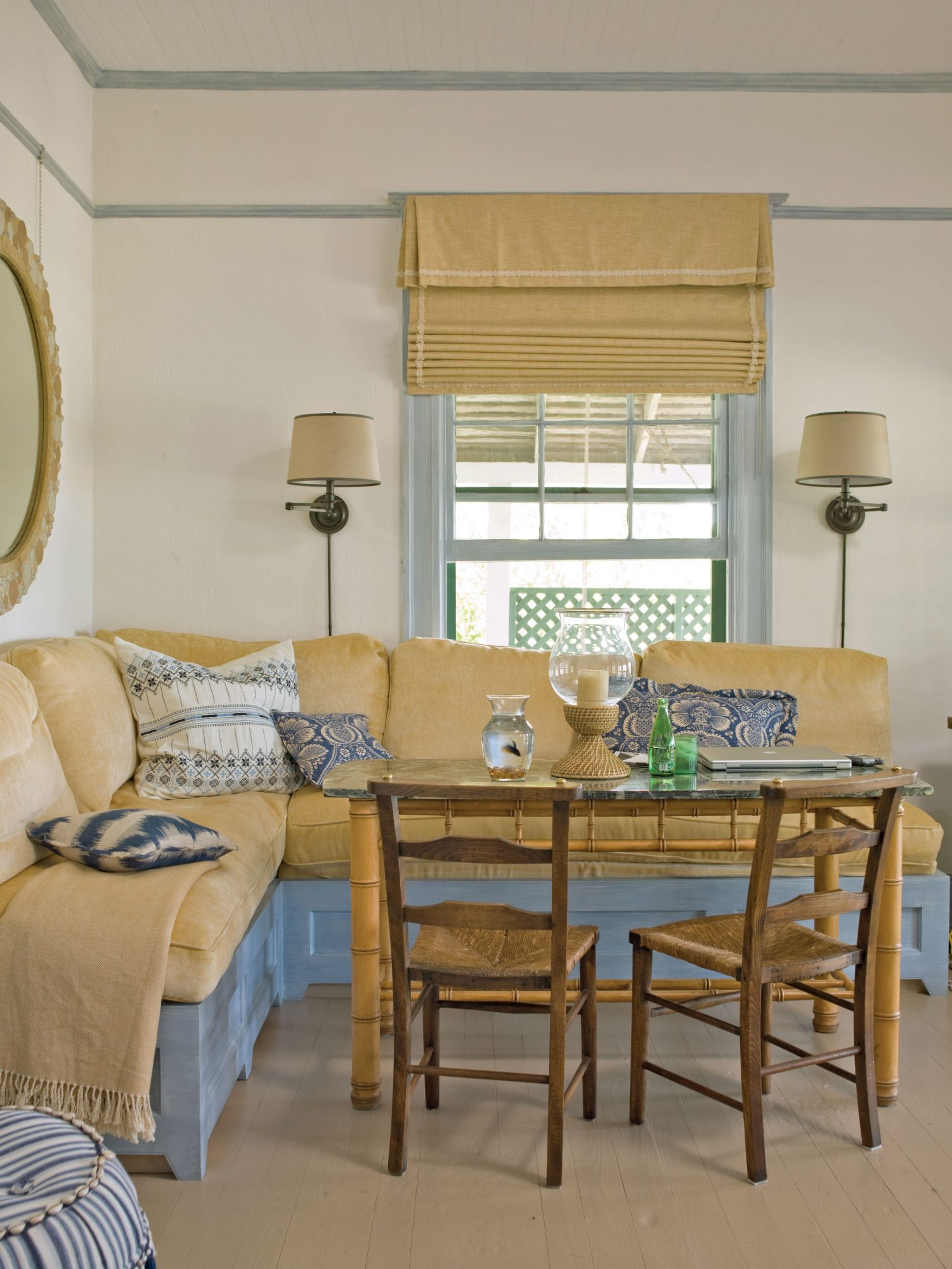 This plush seating area sees frequent use for eating or for a cozy reading nook or office. The natural golden shade of the cushions forgives sandy feet, and the glossy paint on the wood floors is ideal for a beach cottage because it's a low-cost, high-charm treatment.