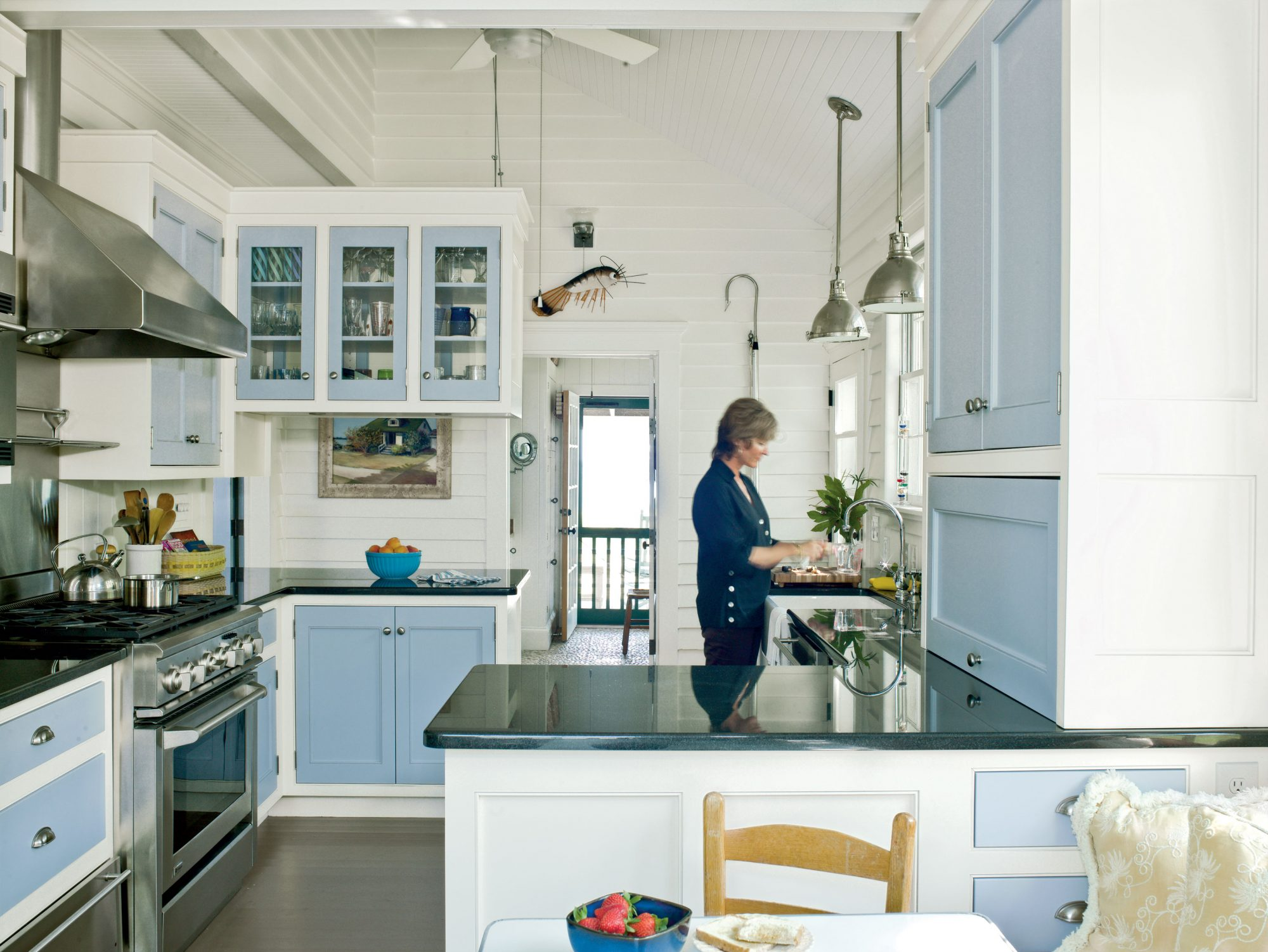 This galley kitchen is made to look larger by using the same shade of paint on the walls and ceiling. Cabinetry doors and drawers are accented in a cheery hue to keep the white kitchen from feeling sterile. Horizontal planked wood siding adds character that plain, painted drywall couldn't, and a few coastal-themed decorations, such as the marine-style pendant lights and shrimp sculpture, convey a sense of place without going overboard.