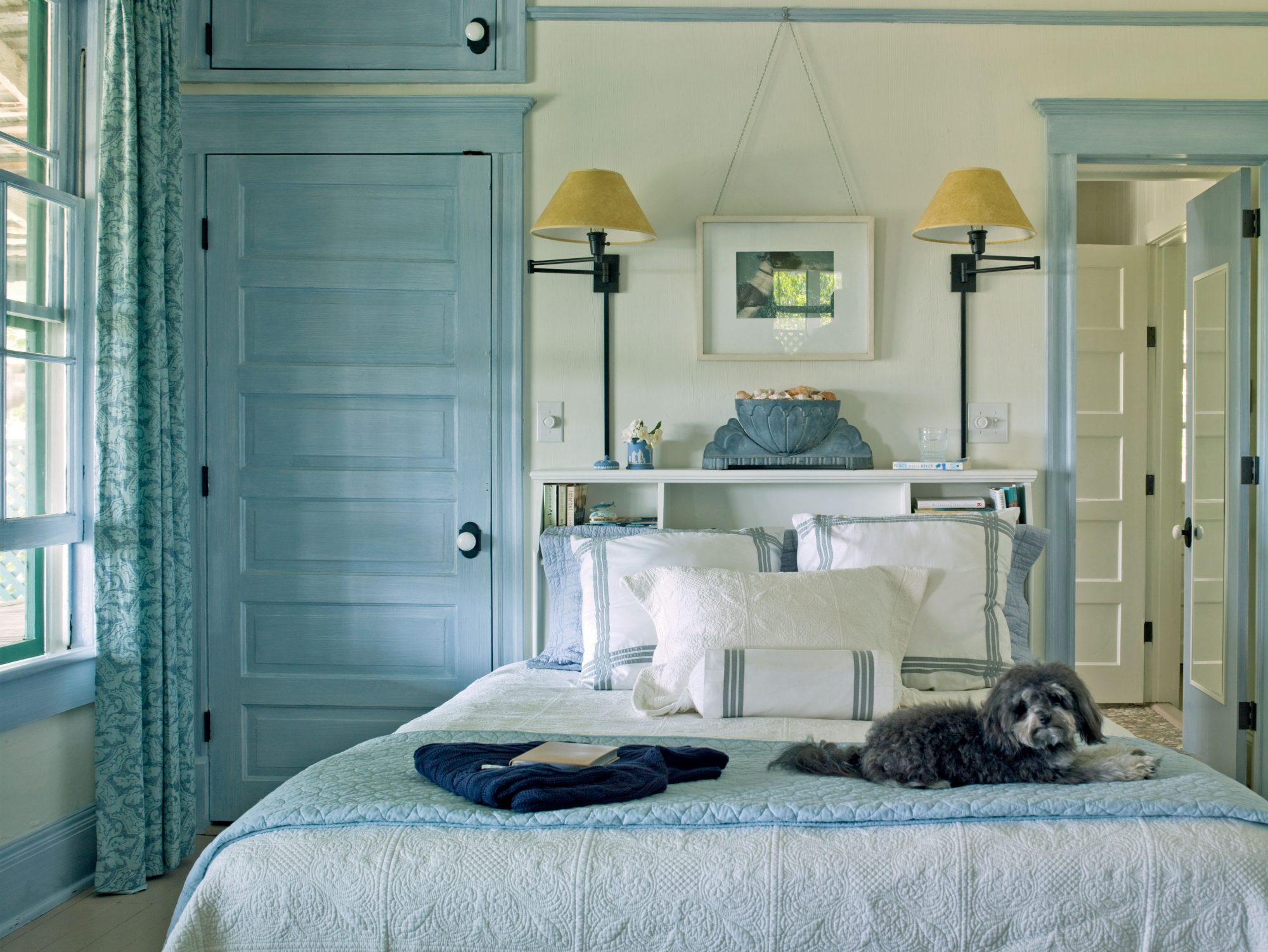 Although the master bedroom is small, the homeowners maximized their space by affixing a headboard that has plenty of shelf space in lieu of floor space-hogging bedside tables. Cool blues and whites make the room seem comforting rather than cramped.