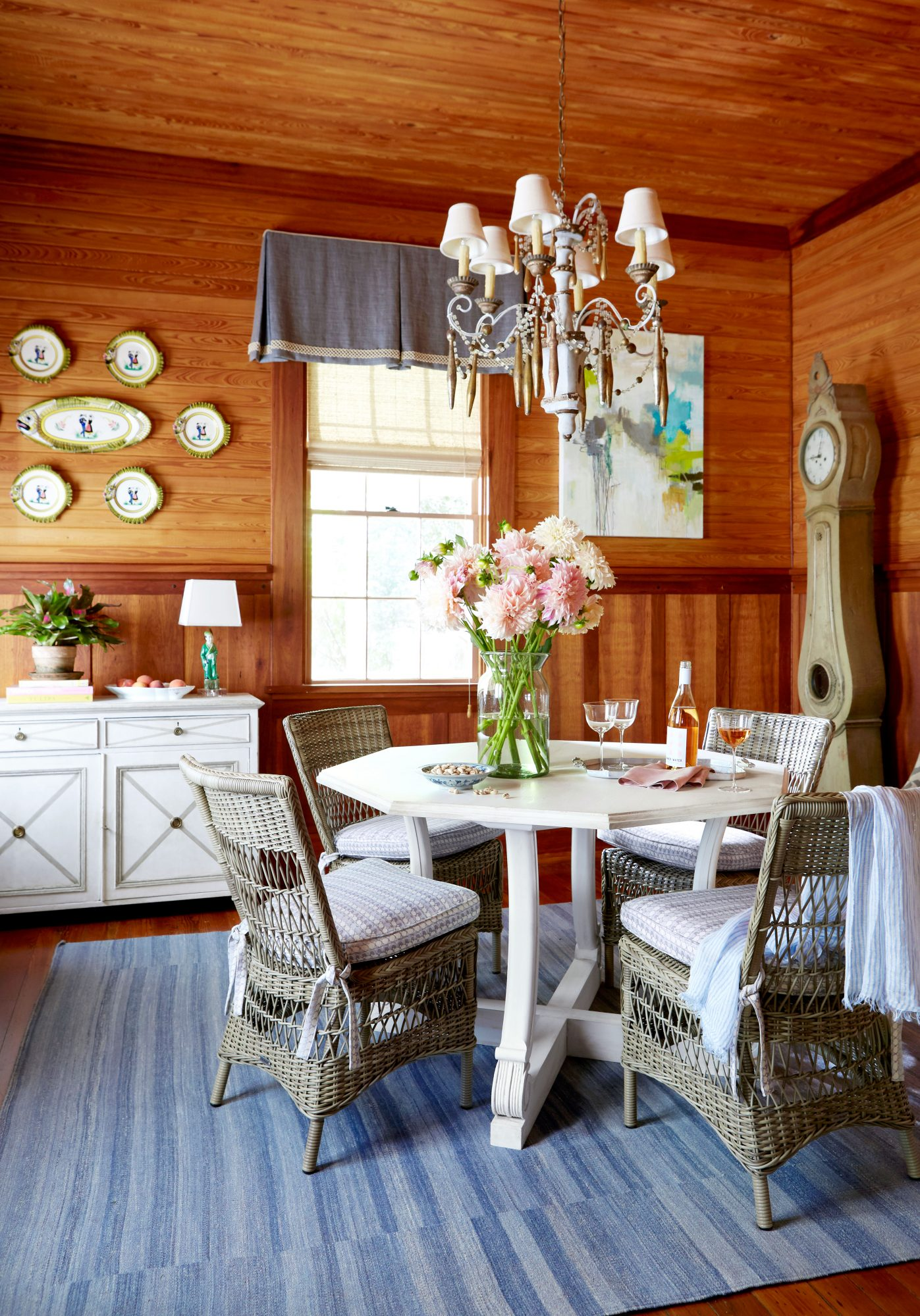 Wood-Clad Dining Room with Round White Table and Wicker Chairs