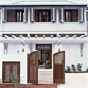 Louvered shutters quickly fixed the air flow problem, and a white stucco exterior with dark wood accents brings on the beachy vibes.
