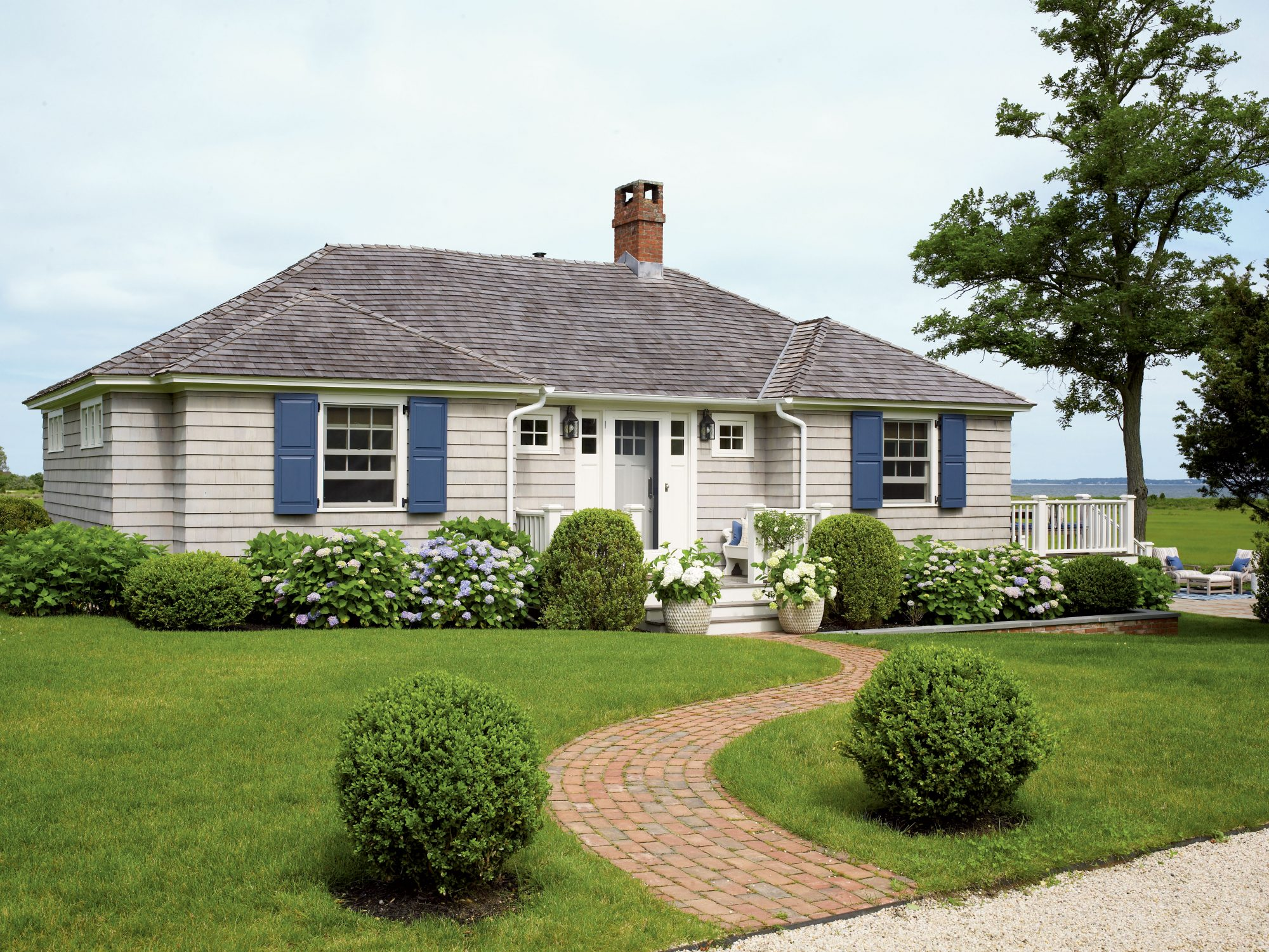 A new gray roof, cozy blue shutters, and pretty shrubs wrapping the house give this cottage contrast—and the welcoming aesthetic it deserves.