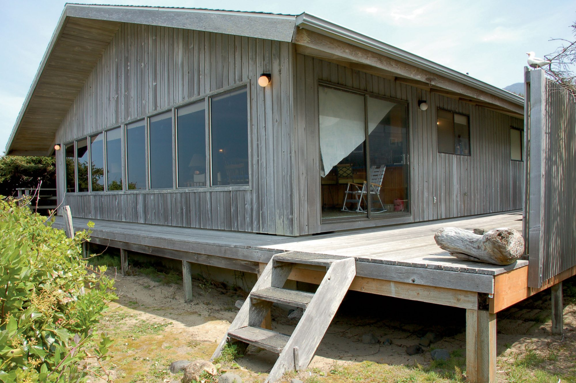 The sun-bleached wooden deck of this home felt uninviting and unusable, with dead space on one side and a view-blocking wall on the other.