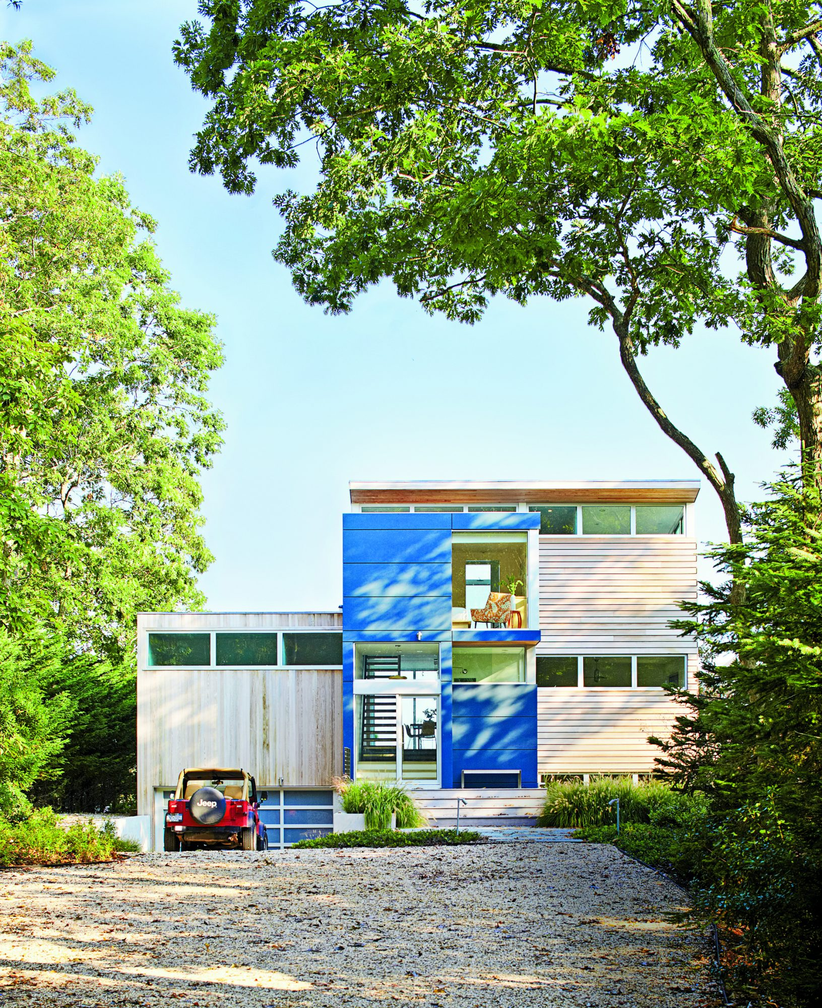 A complete overhaul transformed the cottage into a much more contemporary structure, with lengthy windows, more height, and a fun shade of blue that really pops against the natural wood siding.