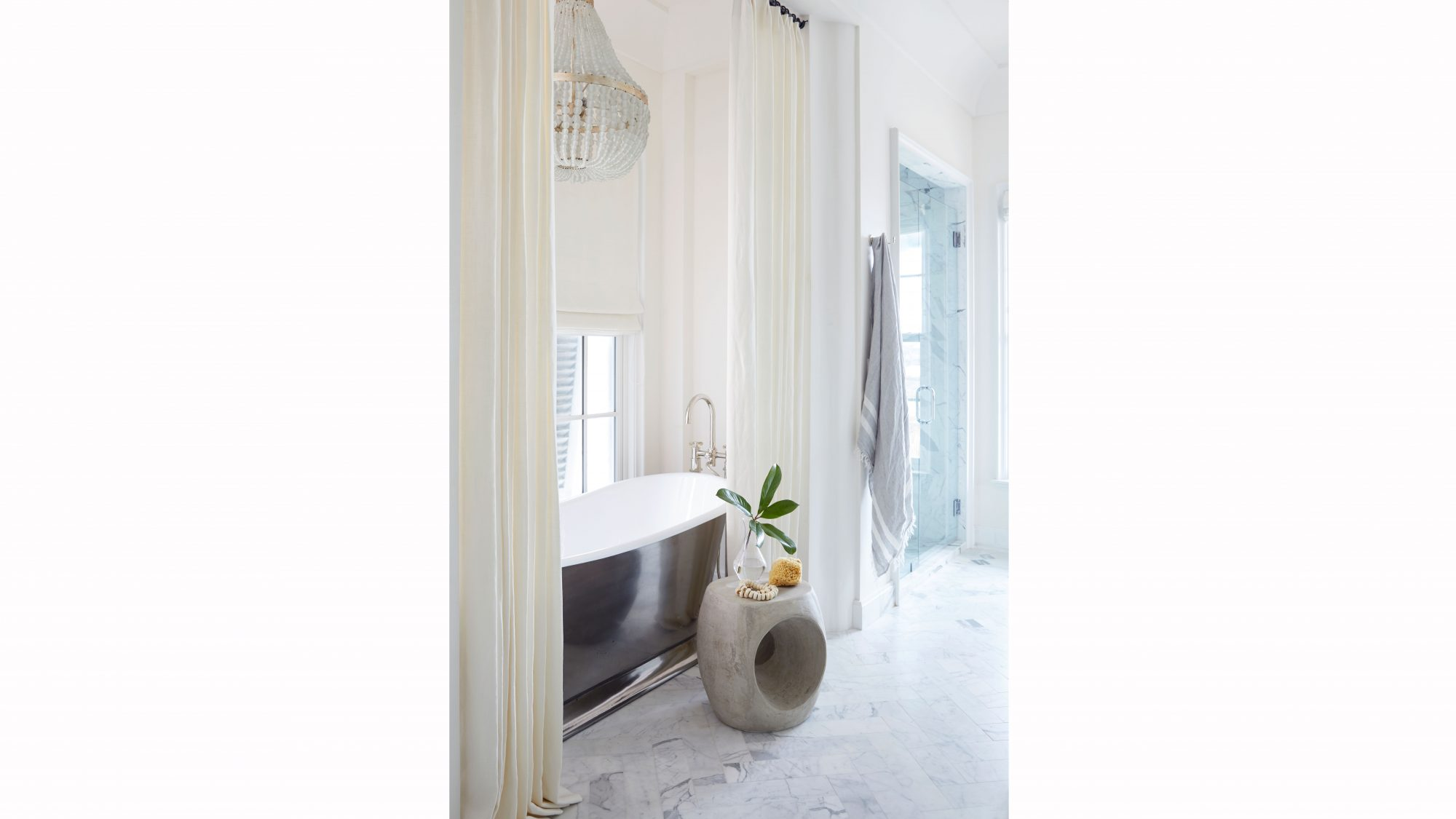 Simple white linens drape the tub in the master bath