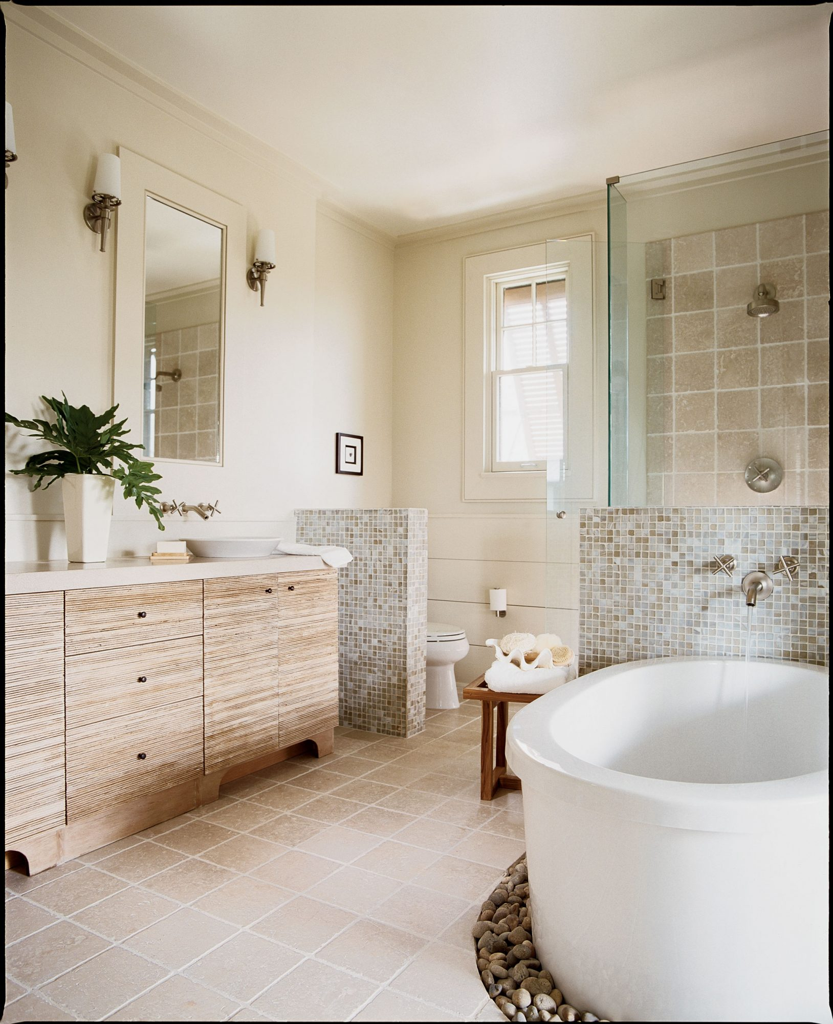 master bath with a freestanding white, modern tub and a glass shower set up behind