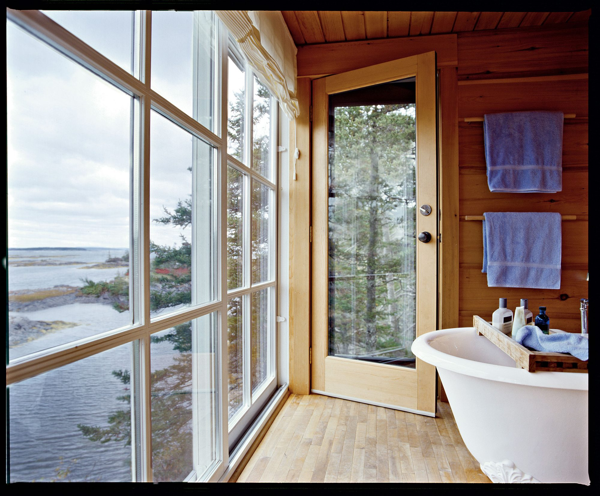 floor to ceiling windows, on one wall, let in plenty of light to a clawfoot porcelain tub while teak wood paneling lines the walls of the bathroom