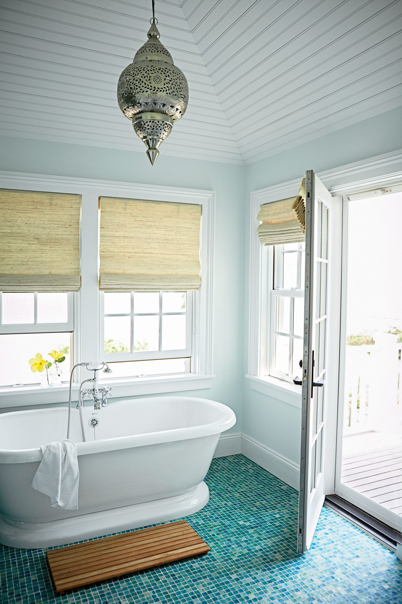 A gorgeous tile floor in a spectrum of ocean-going blues and greens takes center stage in this Long Island master bath.