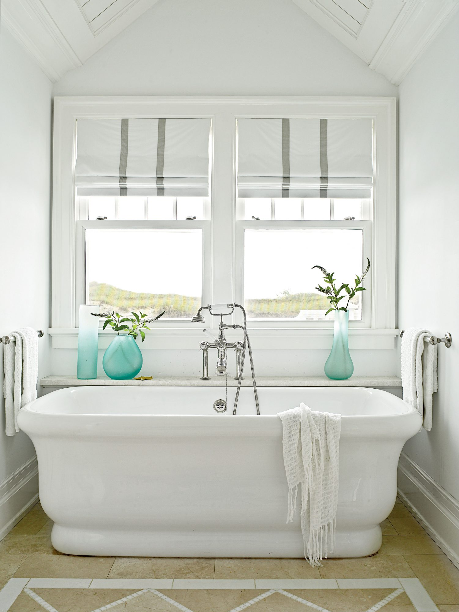 In this master bath, a deep, freestanding tub overlooks the grassy dunes, making it a serene escape.