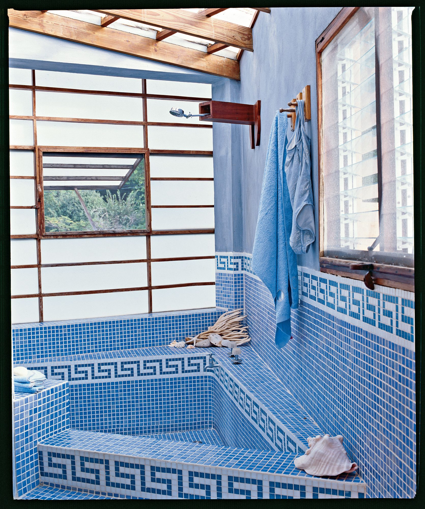 geometric patterns of blue and white tile border the edge of a sunken bathtub covered in small tiles