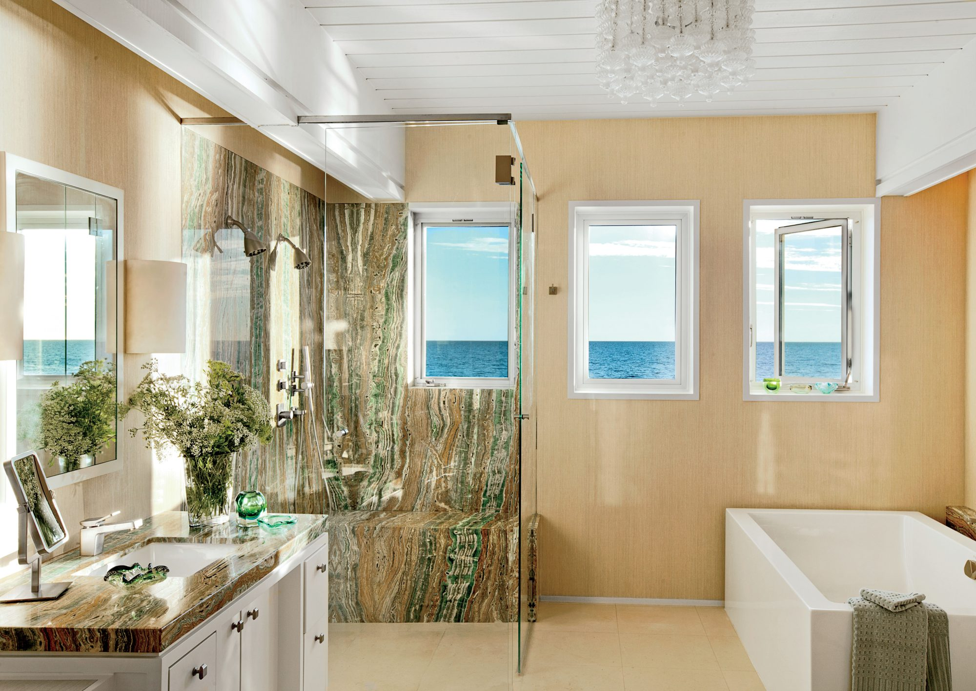 This Malibu master bath got an ultramodern update grounded in clean rectangular lines that are repeated in the soaking tub, a trio of casement windows, and translucent shower stall. Blue-green Esmeralda onyx shower walls (the marble is from Stone Resource
