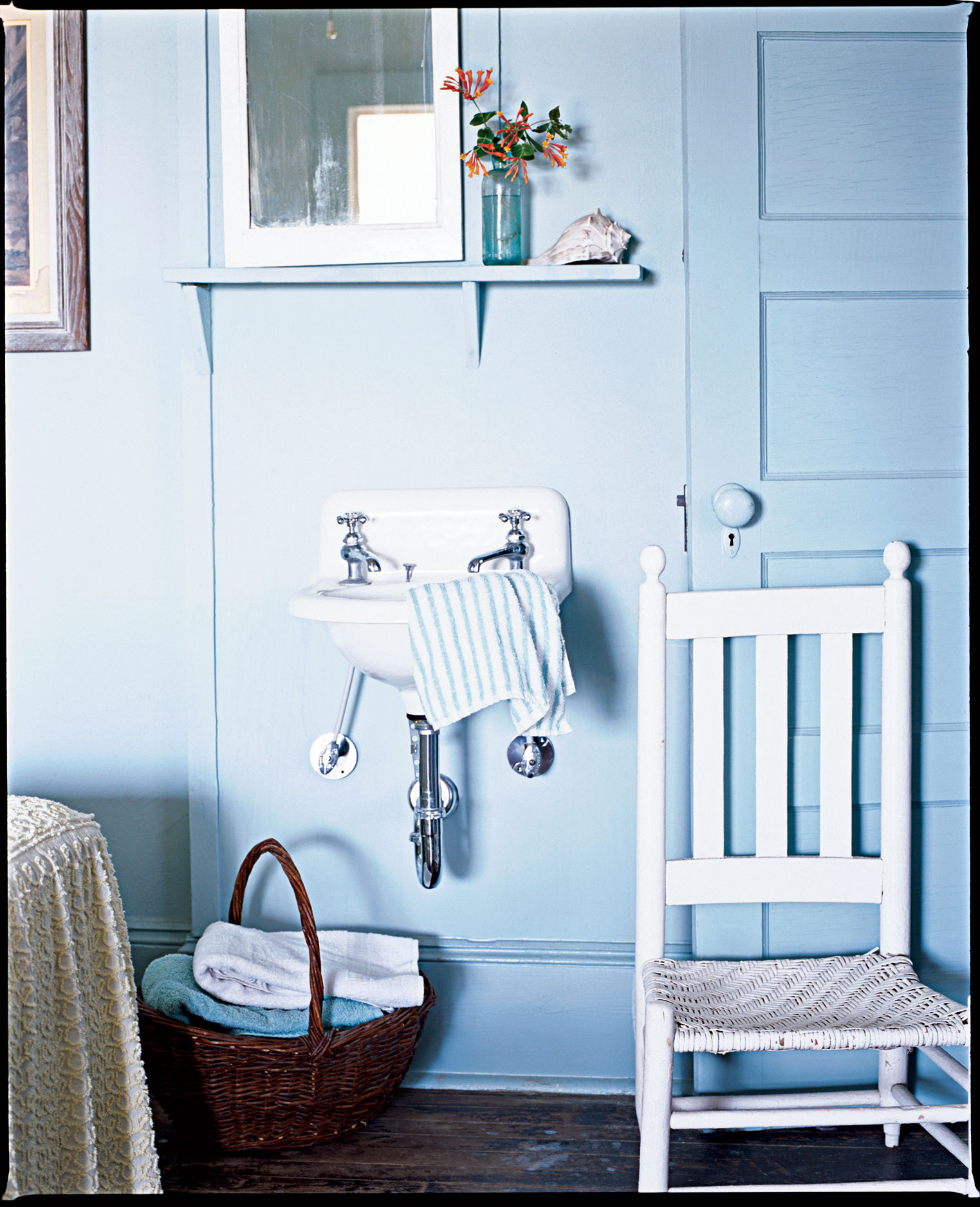 bathroom painted with pale blue paint and a pedestal sink that keeps space open for a small area
