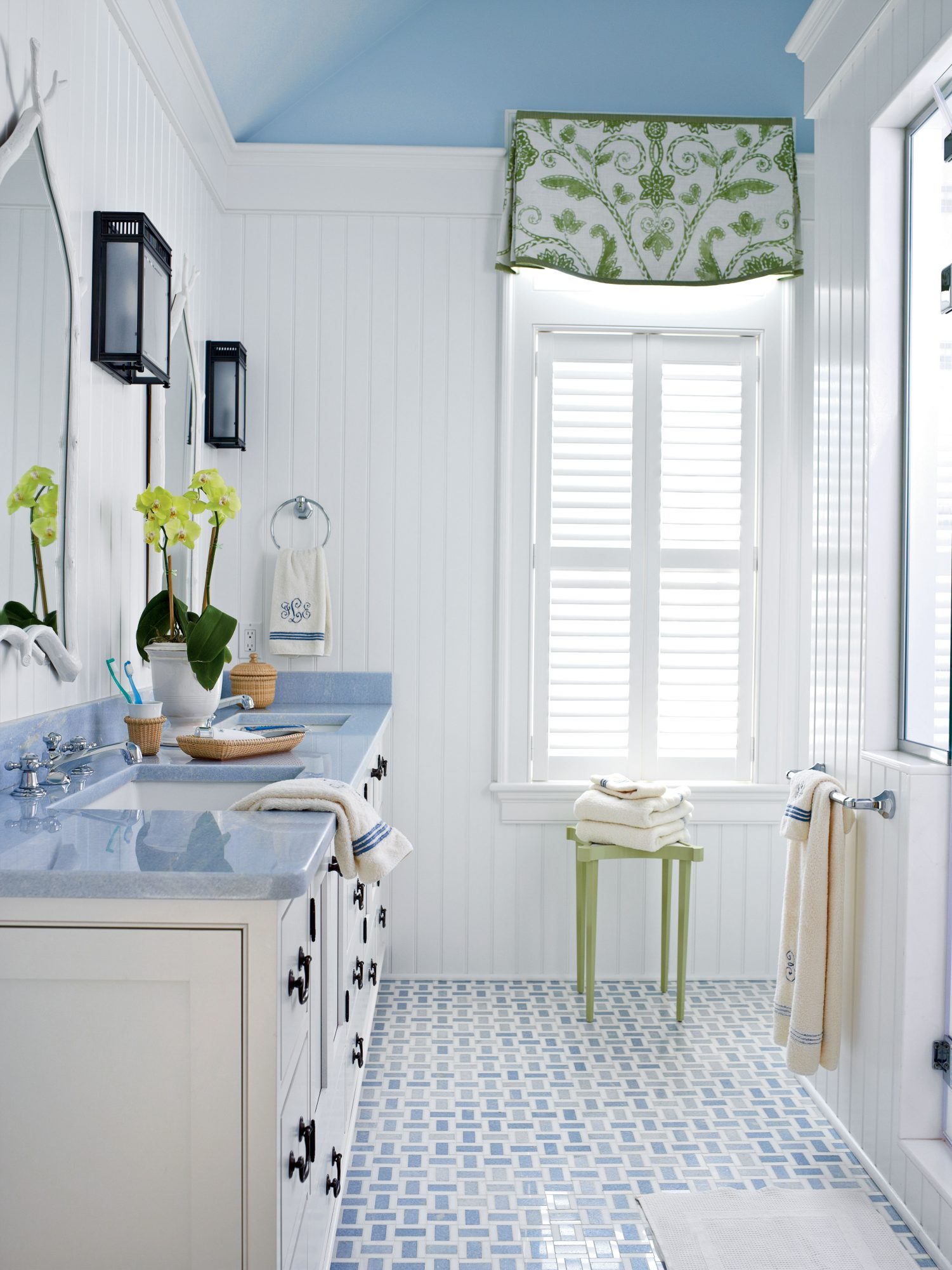 Blue and green accents liven up this pretty white bath. The room appears larger thanks to the vertical boards and the painted ceiling.