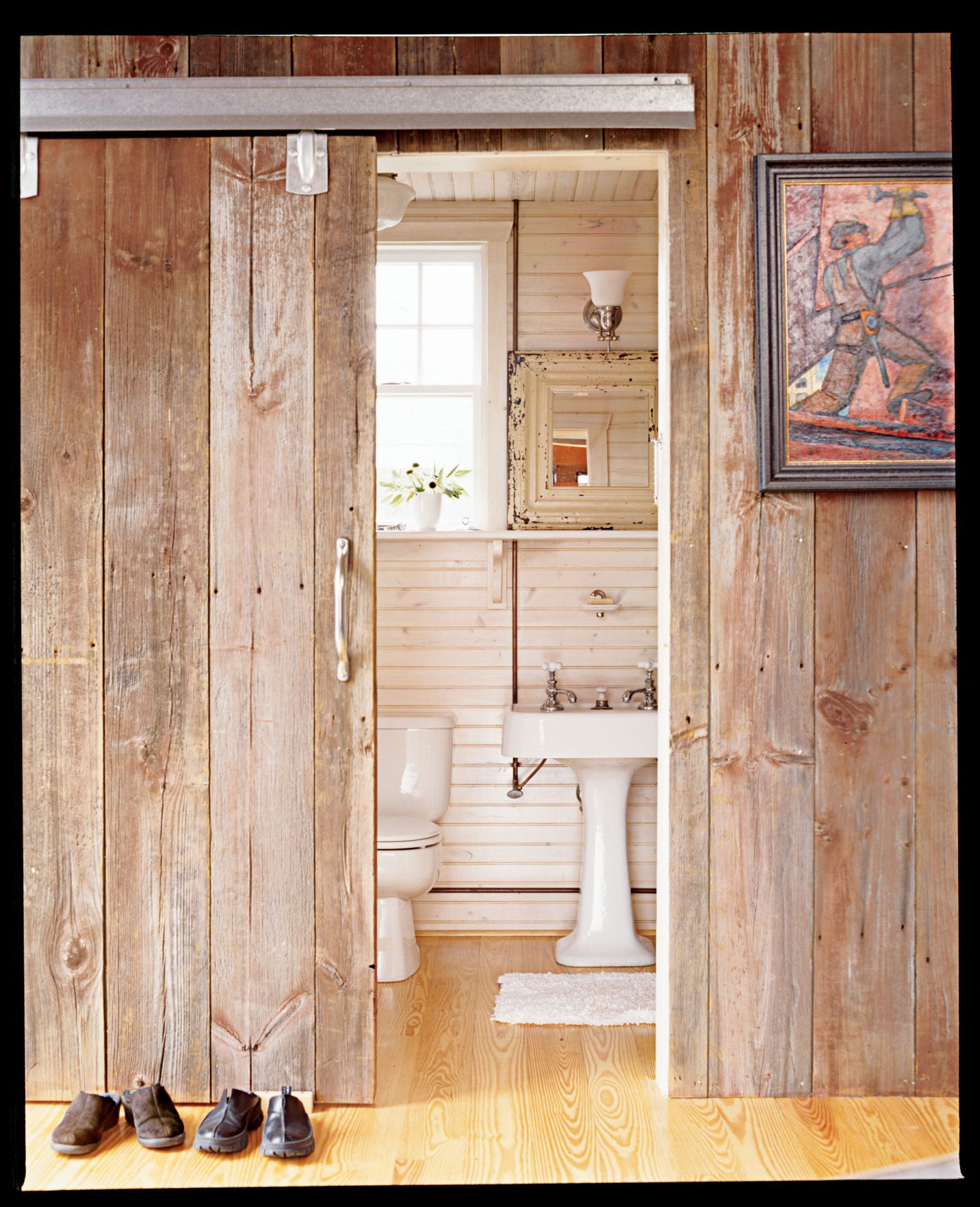 a sliding door opens up to a small bathroom lined in pale wood with a bathroom mirror framed with aged, creamy molding to surround it