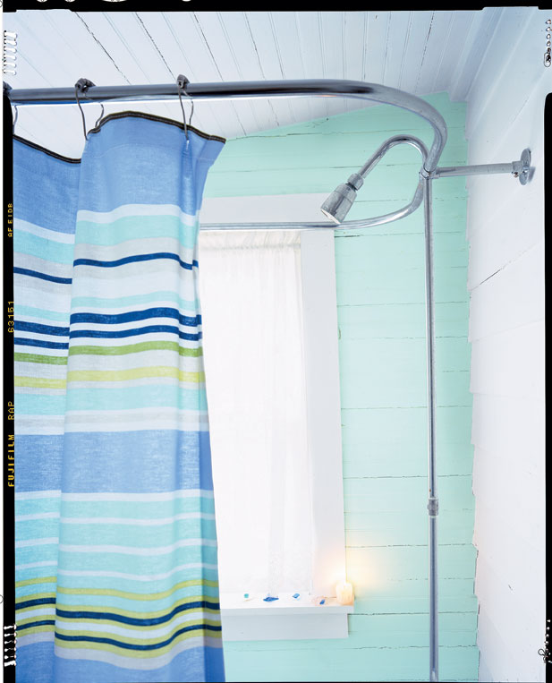 horizontal striped in blue, sea green, yellow and white shower curtain hangs in a beach house bathroom with acqua walls