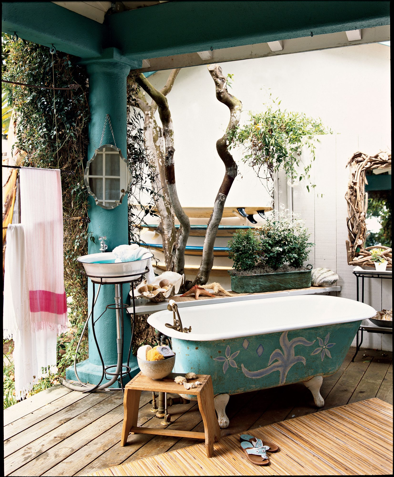 a clawfoot tub sits outside on a deck alongside a standing a pedestal sink with beach towels, a mirror and other accessories close at hand
