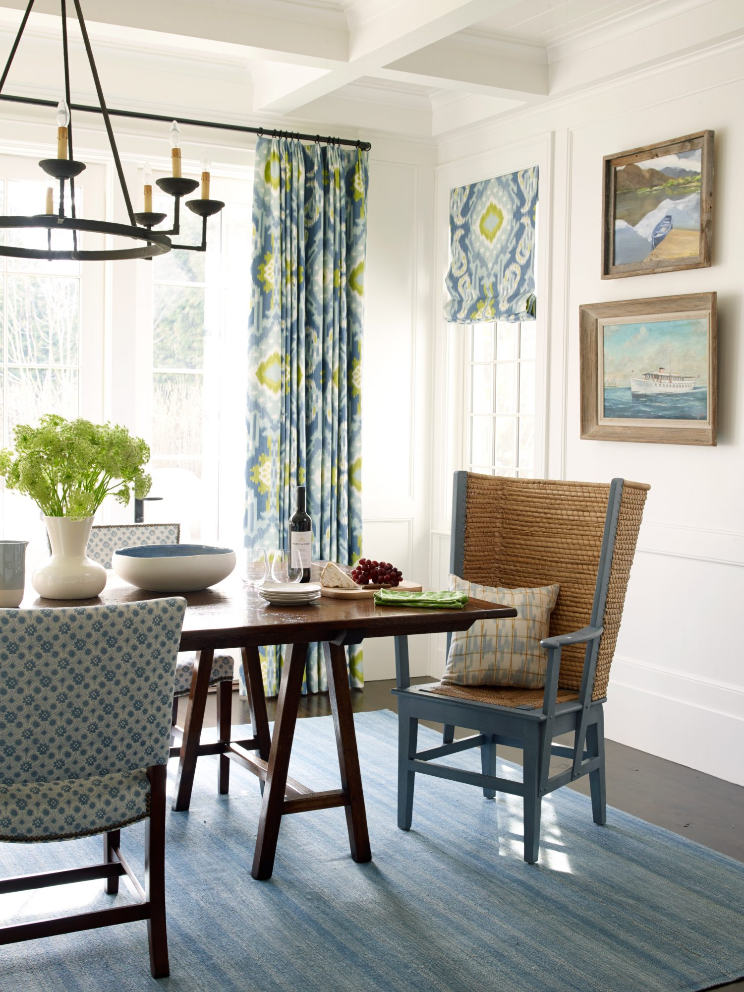Blue always works in a beach house because it relates well to the ocean. Seascapes, a striped rug, and upholstered side chairs highlight those classic seafaring blues, while the contemporary pattern on the window treatments introduces a complementary zippy green to the mix.                             Idea Spotlight                             Antique-inspired furniture is great for giving a little patina and soul to a space. In this East Hampton dining room, a reproduction sawhorse table with hand-hewn planks and a dusty blue Orkney host chair do the trick.