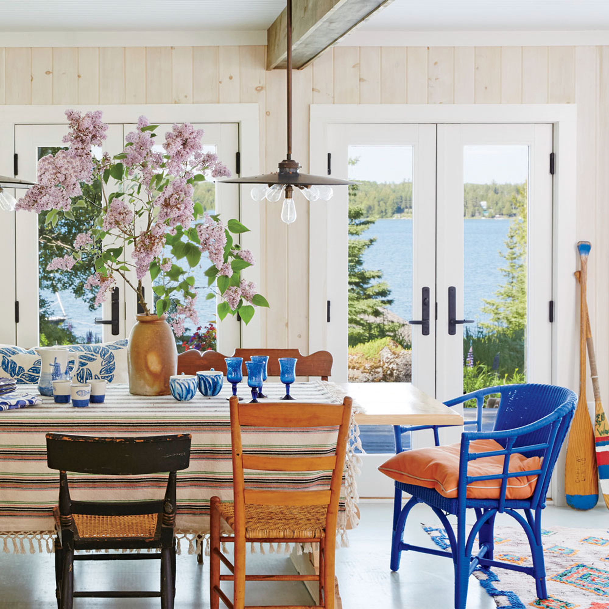 Light wood walls, painted gray floors, and windowed French doors keep the focus on the view in this lake-front dining room, while shipshape accent and vibrant textiles deliver colorful character.                             Idea Spotlight                             Choose a variety of chairs for a dining room set that feels collected and curated over time. All the better if you bring in a wild-card end chair, like the cobalt blue wicker number in this storied Michigan cottage.