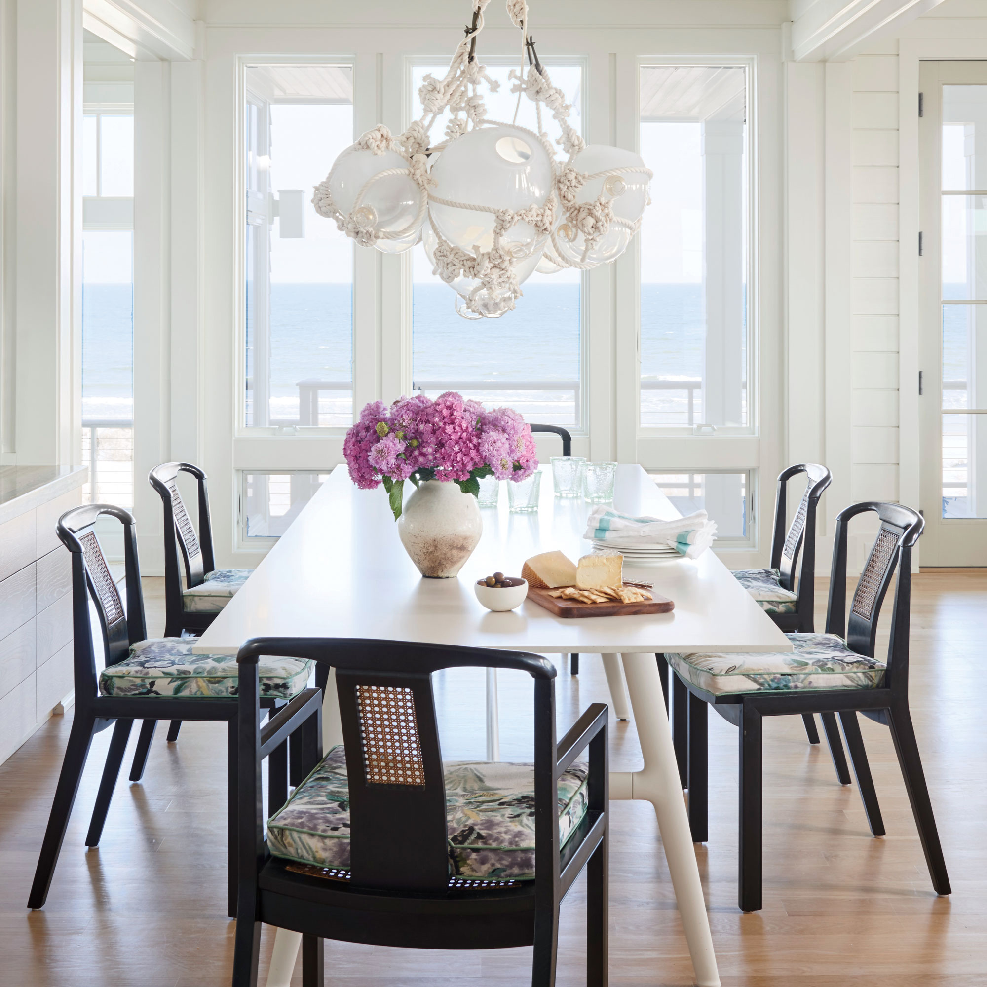 A predominantly white color palette gets its kicks from ebony chairs with cushions upholstered in jewel-tone florals. A sculptural glass-float chandelier by Lindsey Adelman brings in depth and texture without adding competing colors or patterns.                              Idea Spotlight                             Maintain a low profile. In this Figure Eight Island, North Carolina, dining room, vintage splat-back chairs and a leggy, modern table keep all eyes on the ocean views.