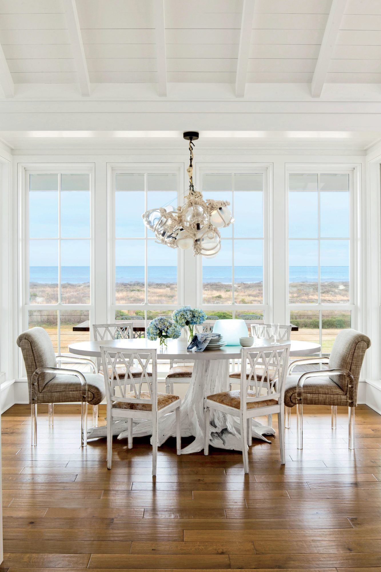 A low-profile table, armless chairs with clean lines, and a glass-float chandelier keep all eyes on the view, while sturdy upholstered end chairs with acrylic arms add gravitas to the space.                             Idea Spotlight                             Bring the outside in by choosing pieces that highlight the natural landscape through their color or form, like this driftwood-inspiredtable.