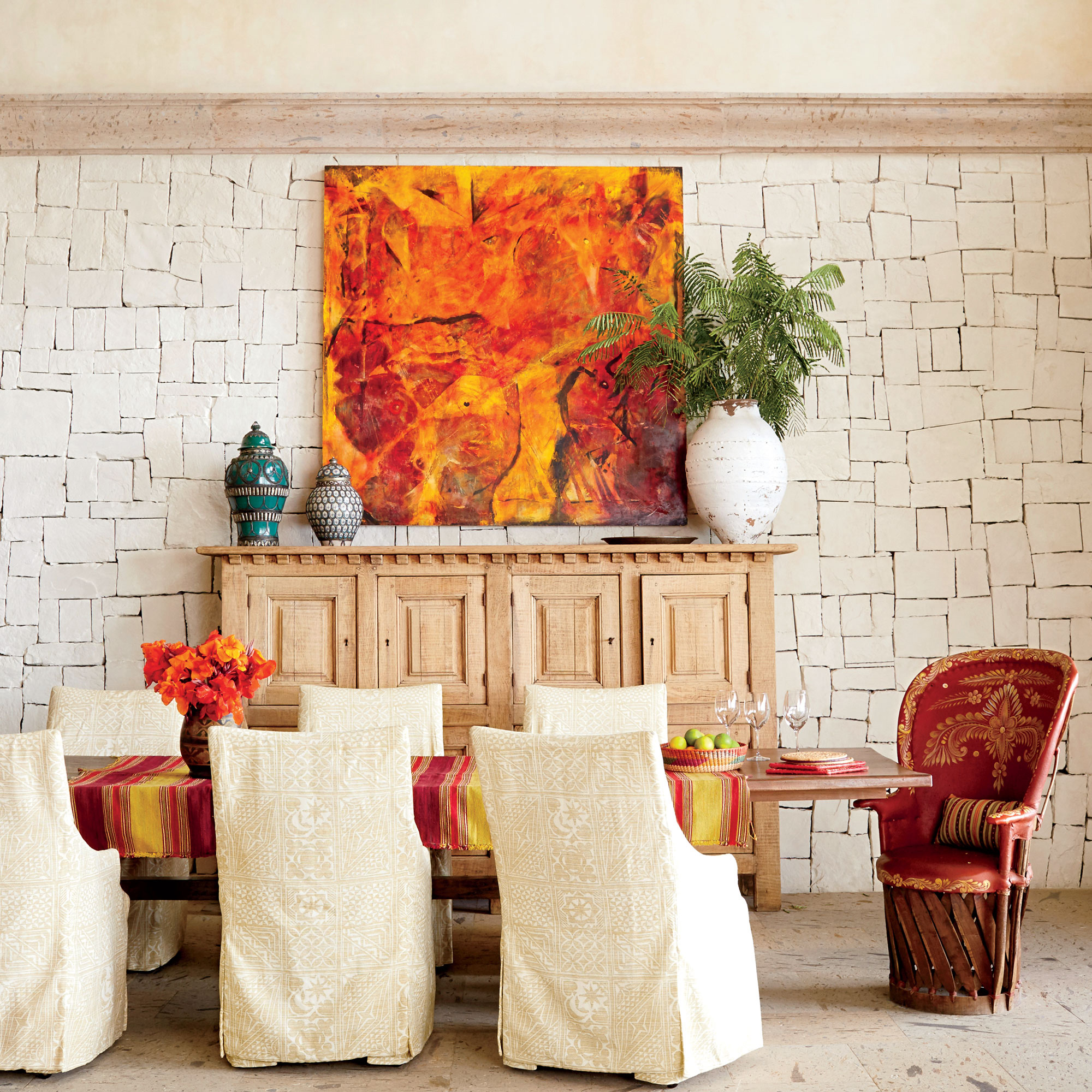 Even a stone wall feels warm and beach house-appropriate when it's whitewashed. The texture of the stone roots the space in warmth and a feeling of age, while off-white linen slipcovers, blond woods, and light floors contribute to the room's bright, airy