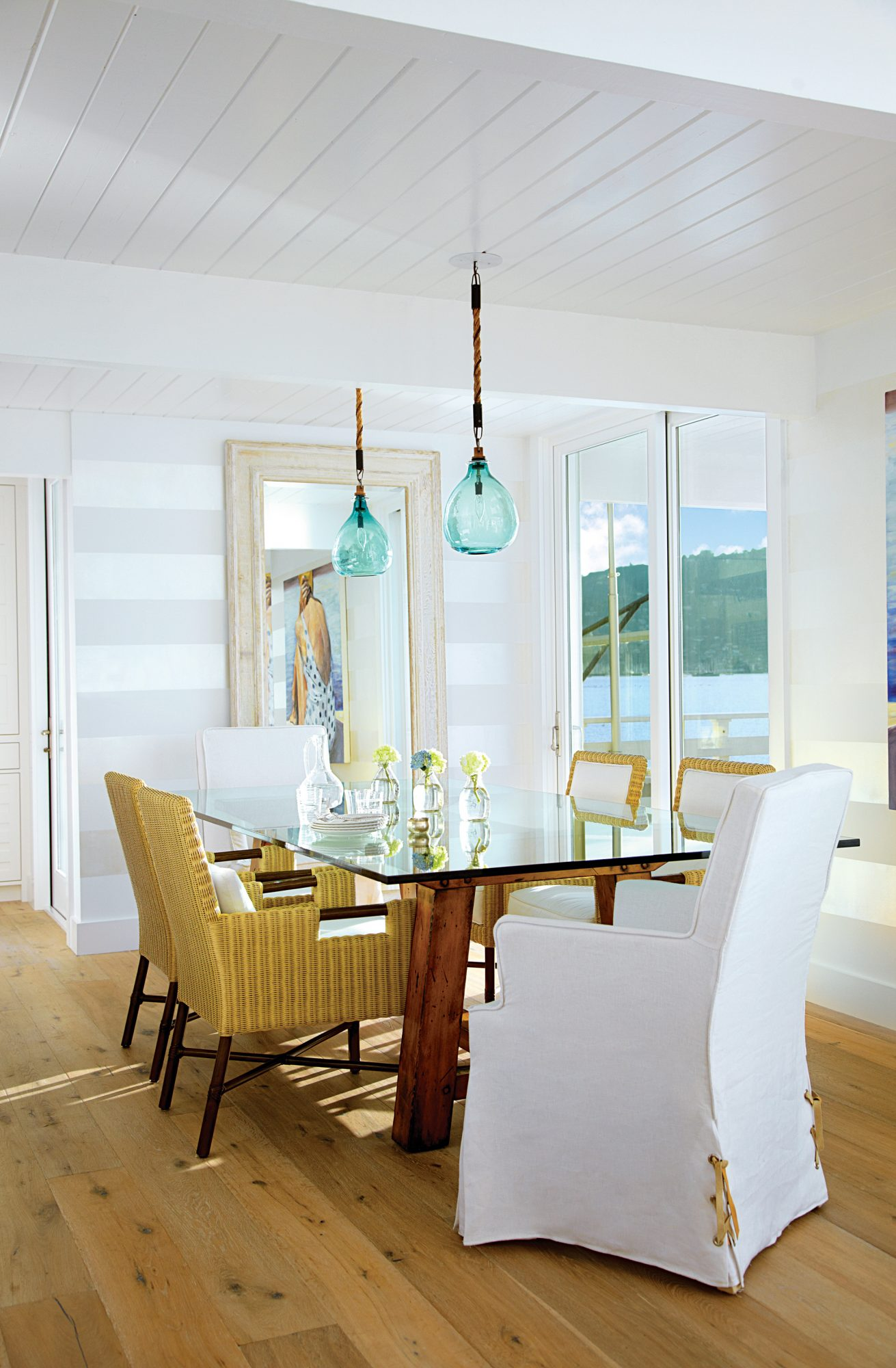 Serenity was the aim in this dining room, so designer and owner Pam Robertson kept it simple. She paired a classic glass-top table with sturdy wooden legs with easygoing slipcovered chairs and deep-seated side chairs, which are perfect for sitting back and enjoying the view.                             Idea Spotlight                             Show your stripes. White walls are warmed up with wide bands of pearly gray in the subdued dining room of this 1960s cottage in Belvedere, California.