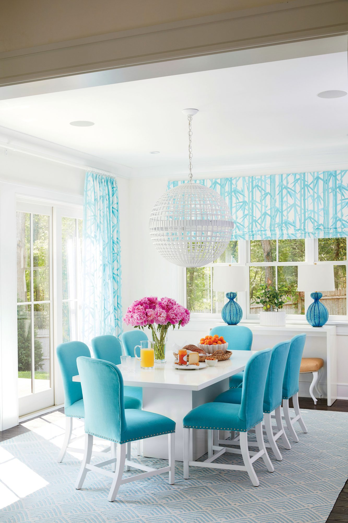 Geometric elements like a striated orb chandelier and angular pedestal-base table convey a strong contemporary vibe. But paired with raffia-upholstered ottomans and curvy sea urchin table lamps, the mod elements strike a more easygoing chord.                             Idea Spotlight                             Frame up your views with knockout-pretty window treatments. In our Hamptons Showhouse dining room, designer Meg Braff used a turquoise-and-white bamboo pattern to draw your eye outside. Plus, the vertical nature of the pattern makes the ceilings feel higher.