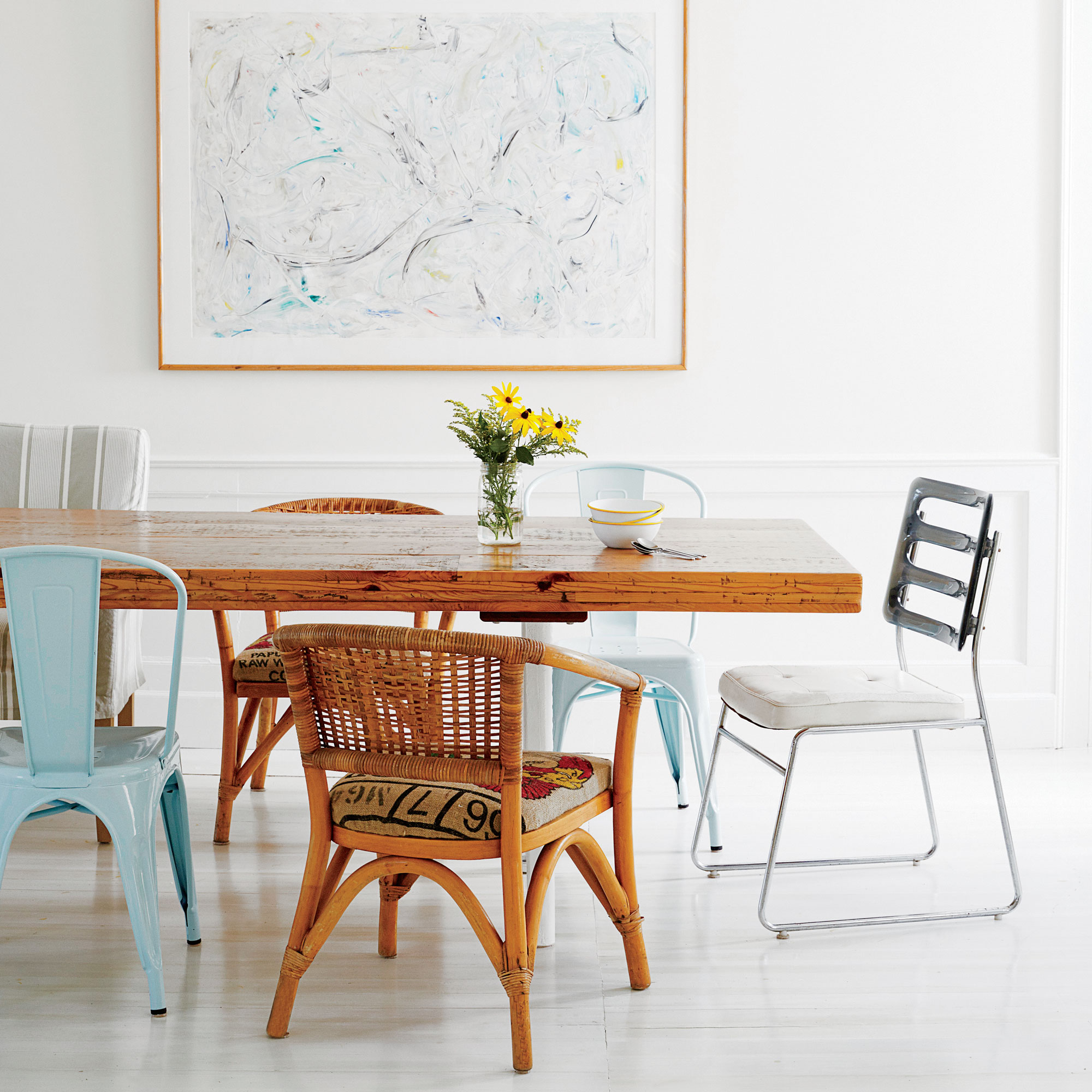 Crisp white walls and light floors create a clean backdrop that nicely contrasts the warm wooden table and a band of chairs in varying materials and colors.                             Idea Spotlight                             Don't be afraid to mix and match. A collection of mismatched chairs and benches (enough to seat 22!) in this dining room makes for a come one, come all atmosphere.