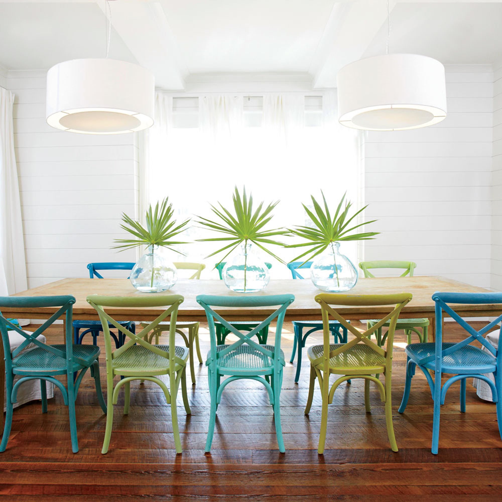 Creamy shiplap walls, mod white pendant lights, and ivory draperies channel bright seaside light, while reclaimed wood floors and a long wooden dining table give the crisp, just-built space a well-worn, well-loved feel.                             Idea Spotlight                             Customize furniture to make it your own. Homeowners Erika Klein and Andrea Alexander spray-painted wooden side chairs from Restoration Hardware in varying shades of blue and green for a cheerful, ultra-casual vibe in their Watersound, Florida dining room.