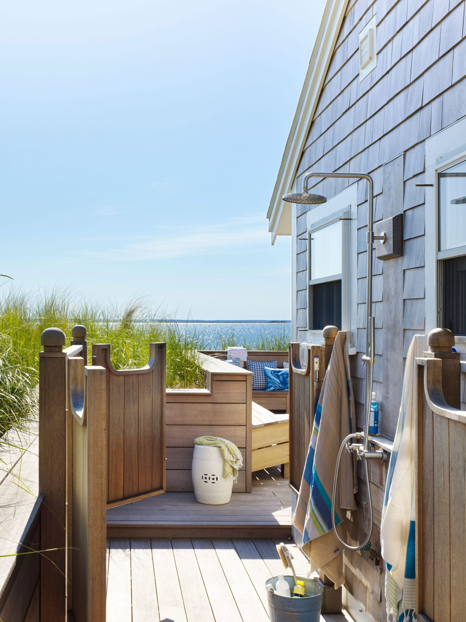 Two sets of swinging saloon doors mark the entry to this tiny Provincetown, Massachusetts, cottage's outdoor shower, which opens up onto a cozy mahogany deck with handy bench seating and stunning ocean views. The designers also installed a foot-wash stati