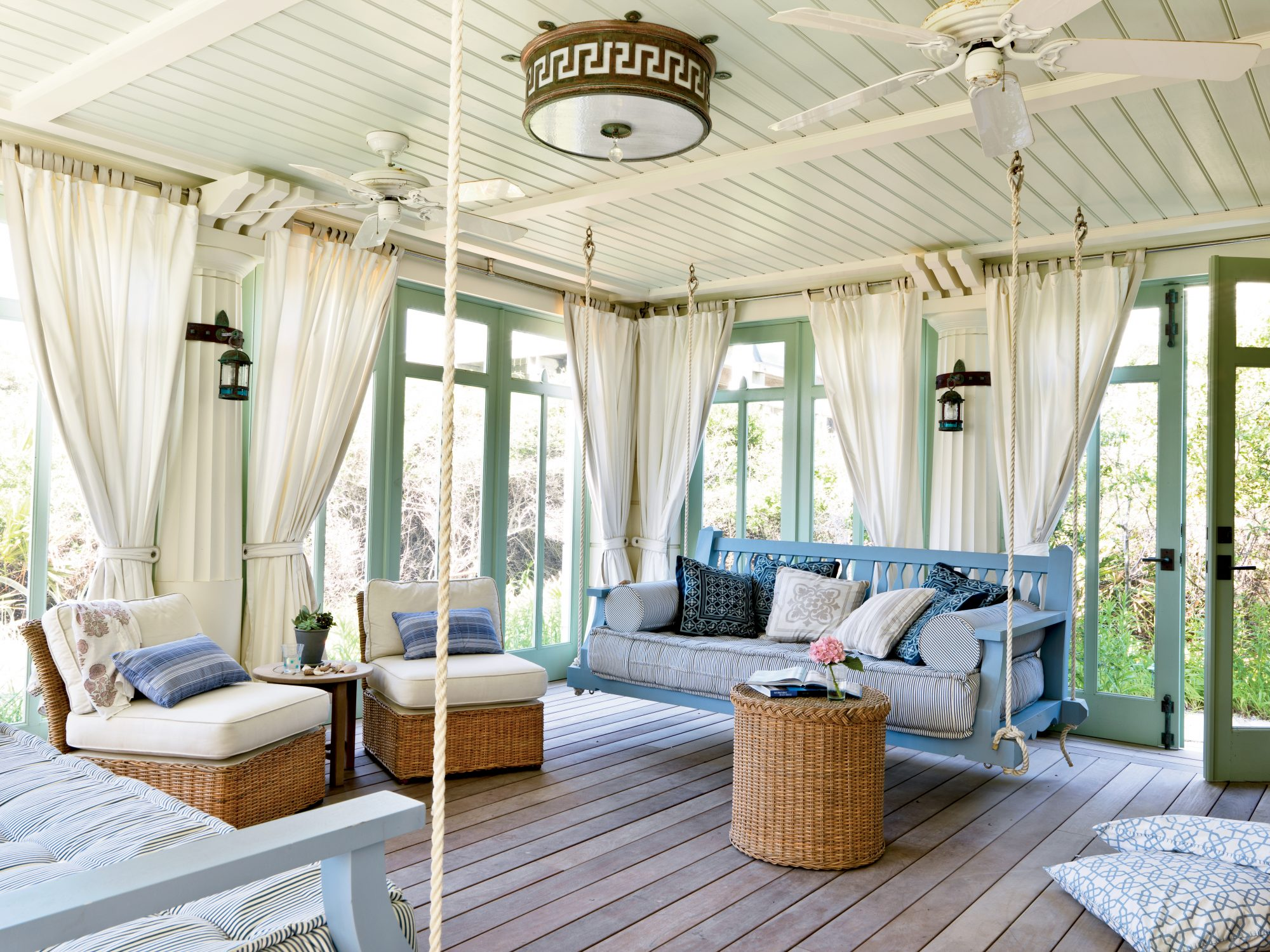 This Seaside, Florida, sleeping porch is the ultimate coastal hangout. It's screened and curtained for comfort and features both hanging daybeds and a pair of wicker chairs with plush cushions. The hanging beds are outfitted with a thick cushion the size