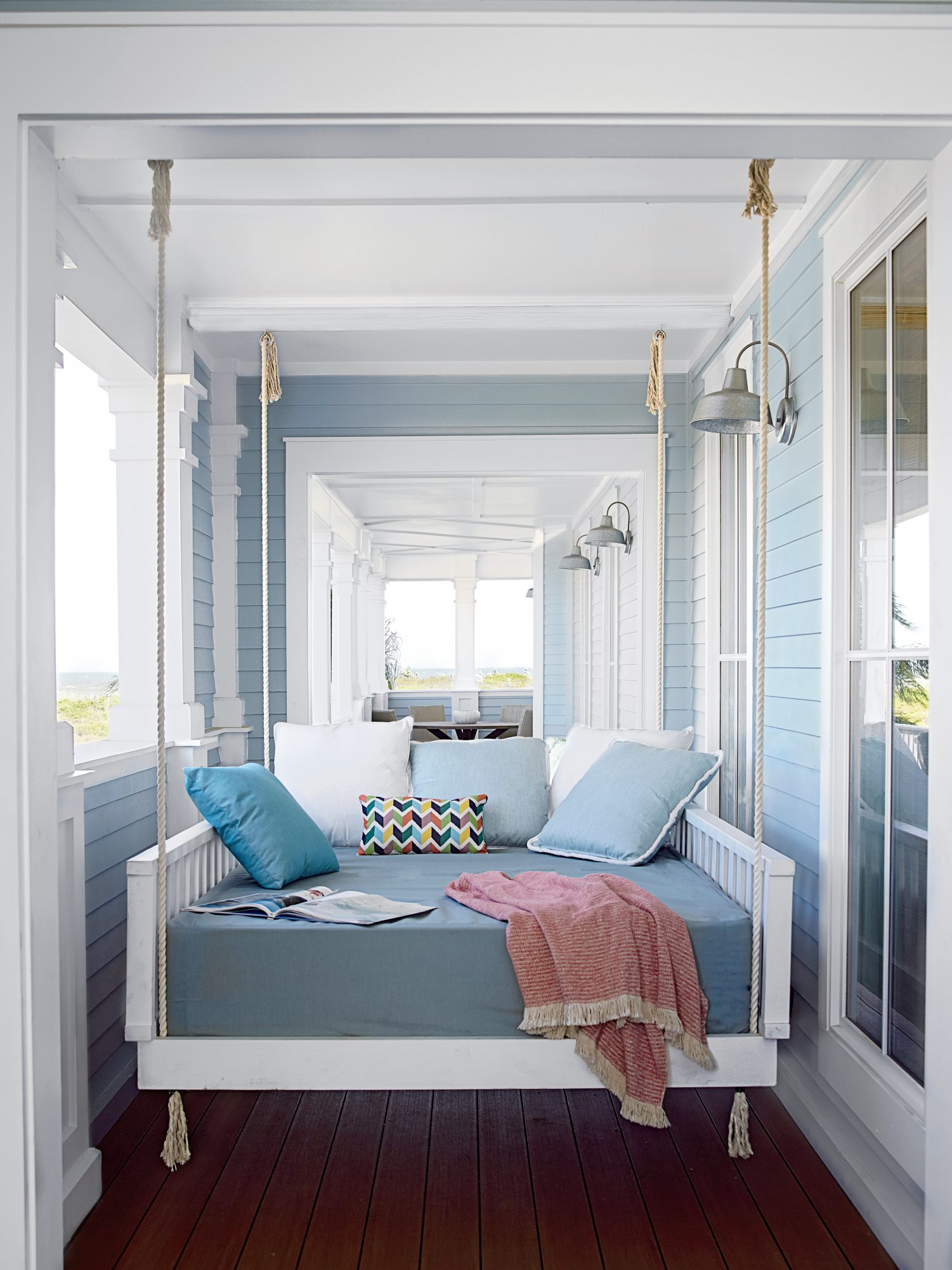 The sleeping porch at our Cinnamon Shore Showhouse in Texas features a custom hanging bed that's ideal for afternoon naps after a day at the beach. Designer Bailey McCarthy—a bedding whiz (she has her own line of sheets, pillows, throws, and more at Biscu