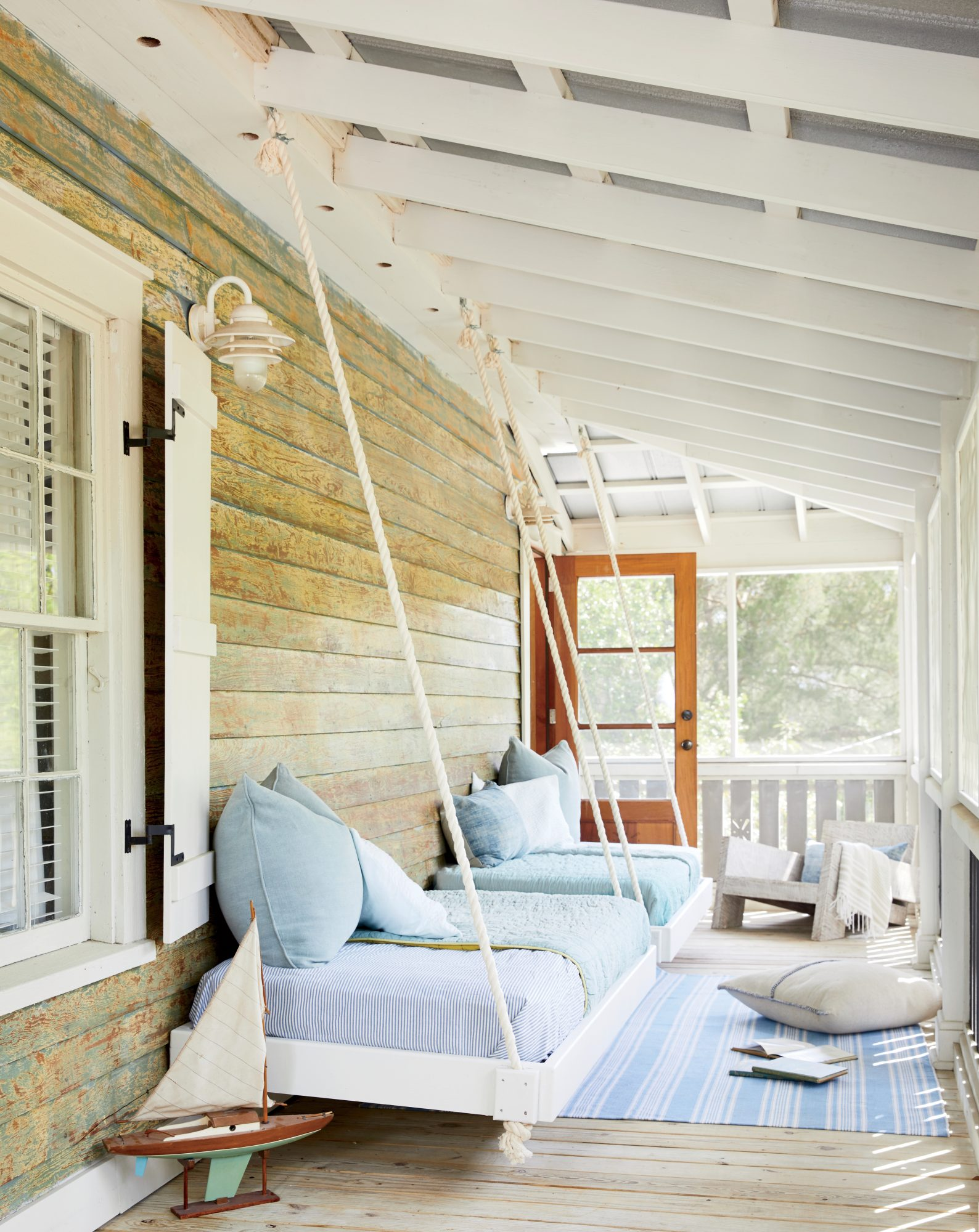 "A breezy corner sleeping porch is outfitted with custom cedar beds, which are secured to the siding and suspended with rope to ""float"" above the floor."