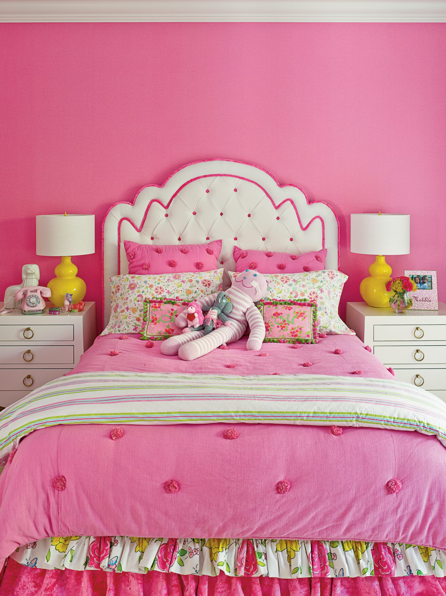 Bright pink wallpaper sets the tone of the daughter's room, where pops of sunny yellow accent the space. The custom headboard, designed by Small, anchors the space.
