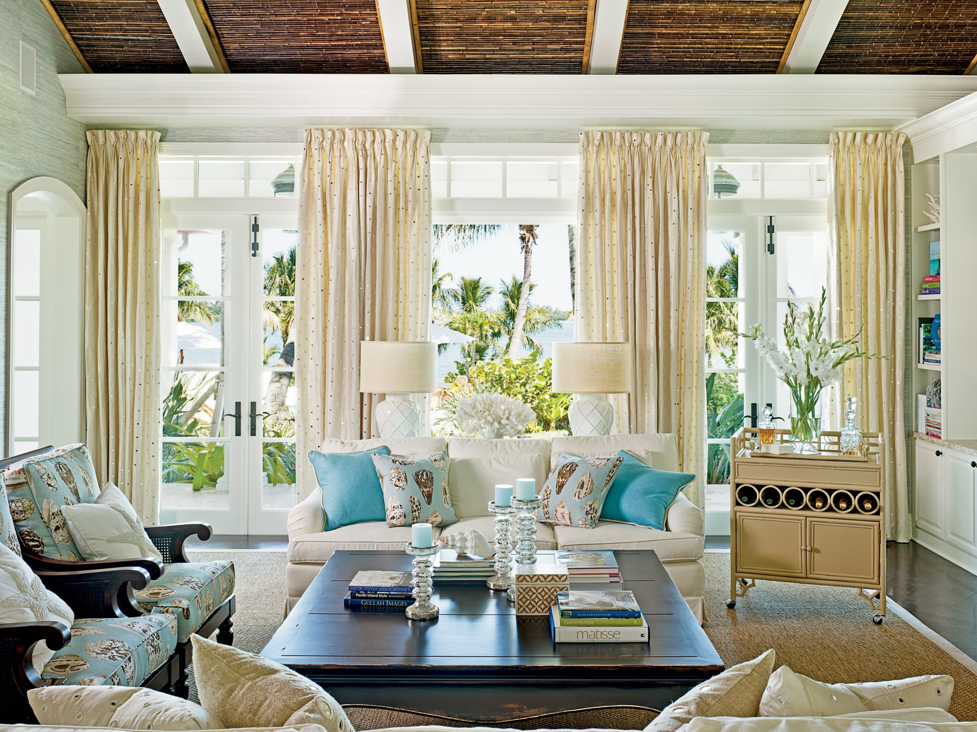 The living room features organic details such as a bamboo ceiling, grasscloth wallcovering by Phillip Jeffries Ltd., and plantation-style wood-and-rattan furnishings.