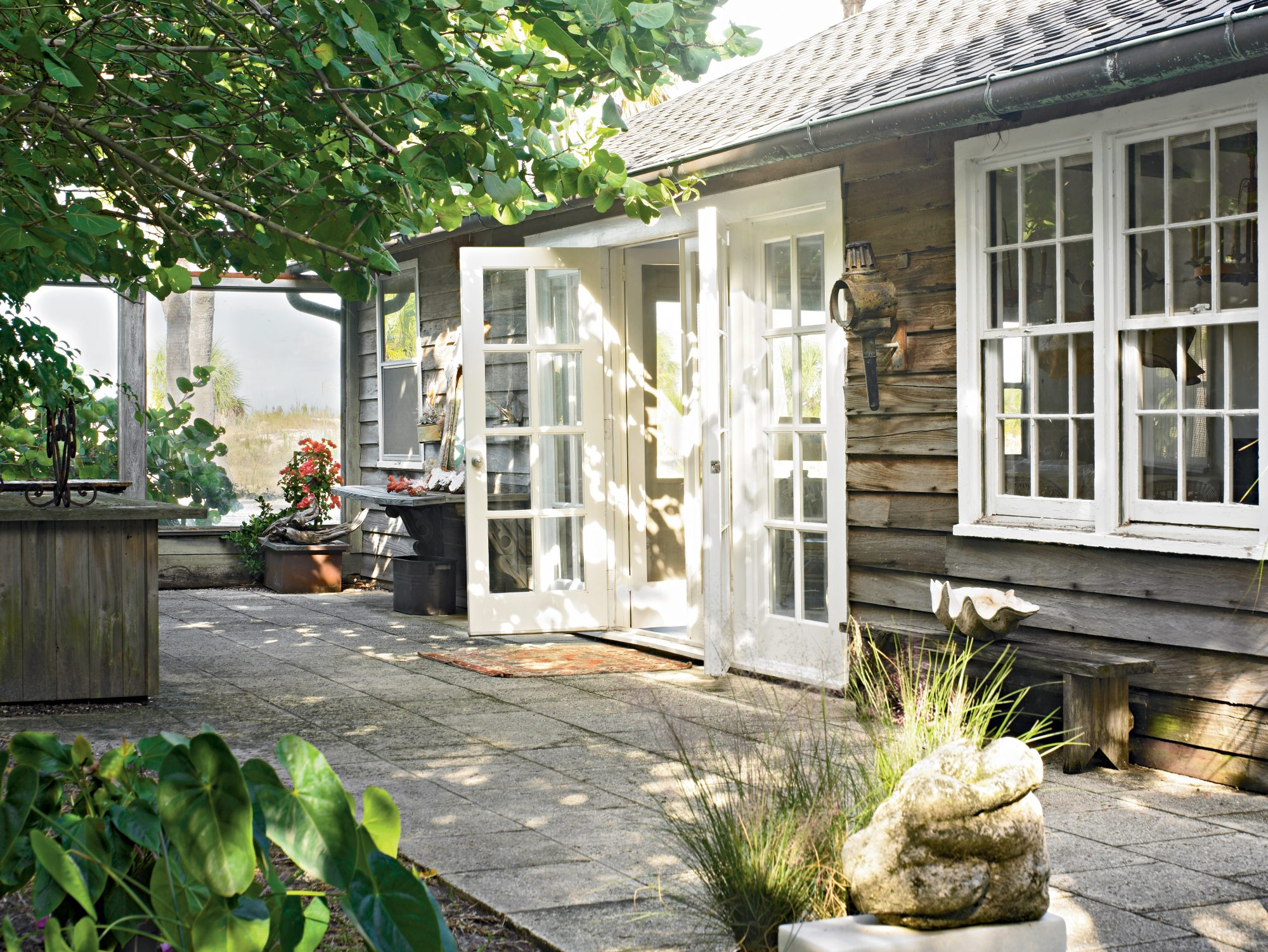 The simple stone slab patio is shaded by large trees and is a lowkey spot for enjoying coastal breezes. The smart white trim on the French doors and windows creates a striking contrast against the weathered wood siding.