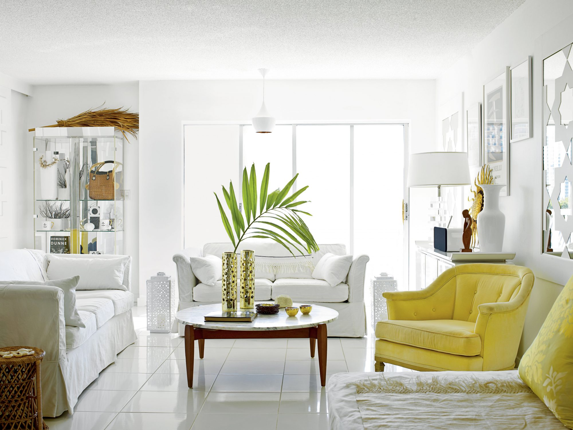 This stylish Miami condo receives the modern treatment with a laid-back, all-white aesthetic. A pop of color from the yellow chair breaks up the pristine palette.