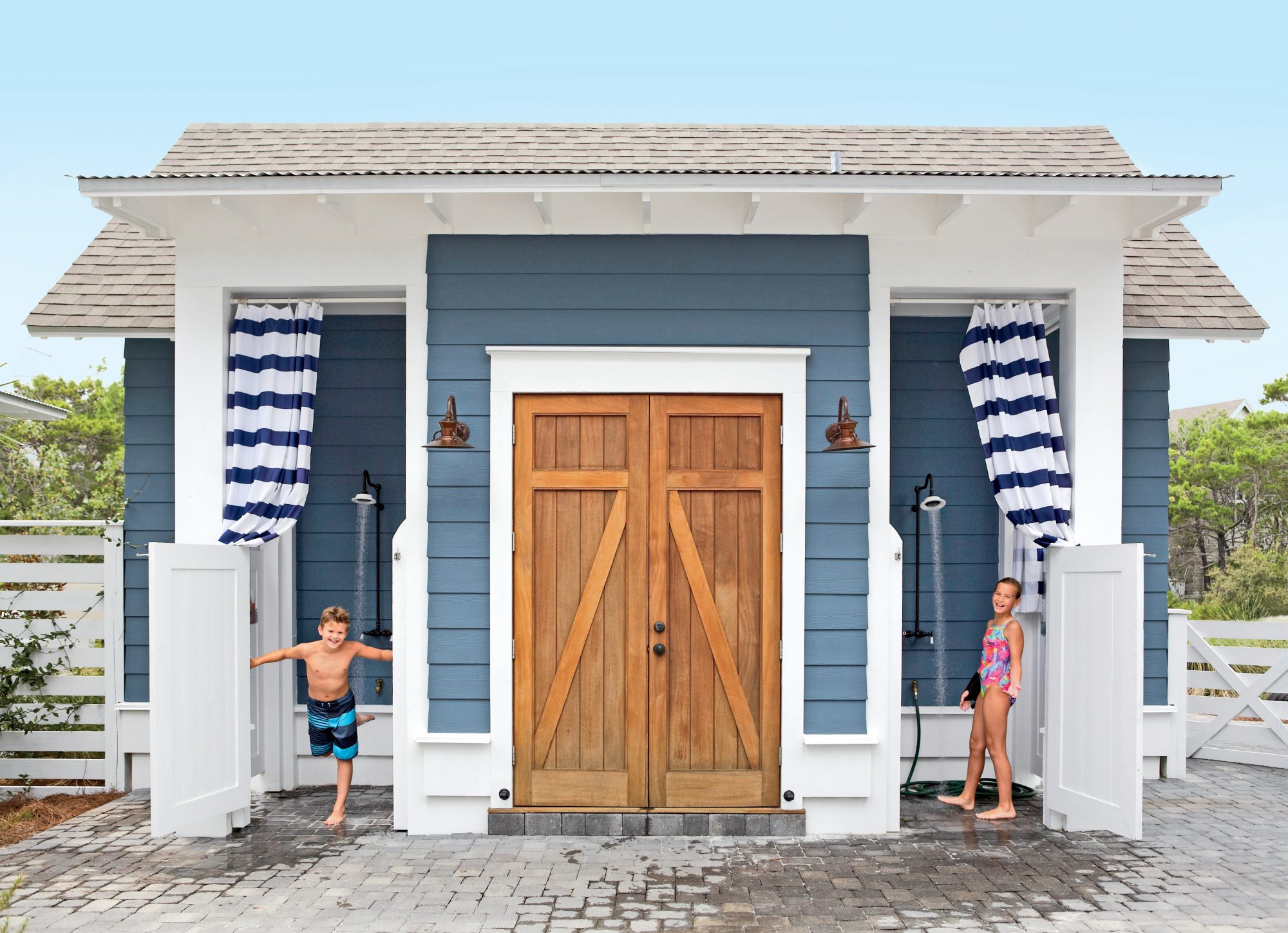 Alongside the driveway of this Watersound, Florida, beach house, a pair of outdoor showers flank a bonus laundry room that's perfect for washing sandy suits and towels. We love the striped curtains, blue siding, sky-high ceilings, swinging saloon-style do
