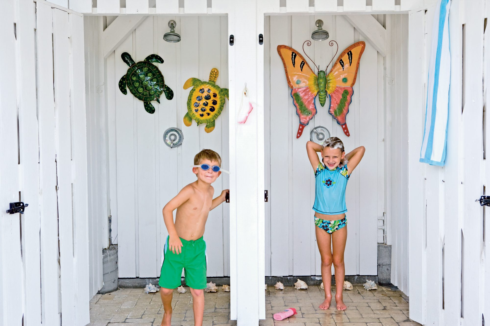For beach homes that host large groups, multiple outdoor shower stalls boost the convenience factor exponentially. Here, board-and-batten walls and locking doors give a finished look and offer privacy. Metal hooks for suits, towels, and gear complete the